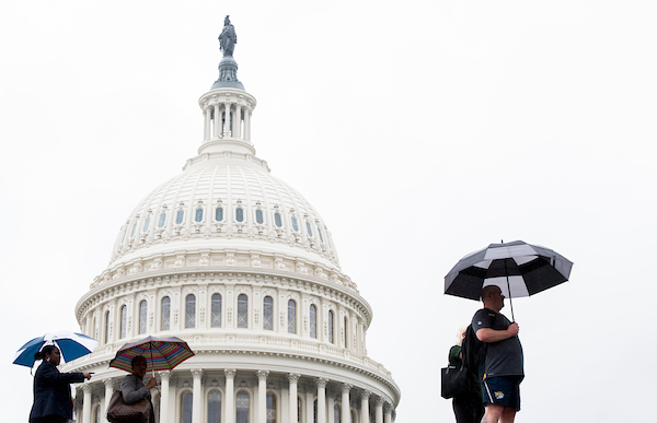 Tourists walk past the dome of the U.S. Capitol as a light rain falls on the Washington area on Wednesday, May 16, 2018. (Photo By Bill Clark/CQ Roll Call)