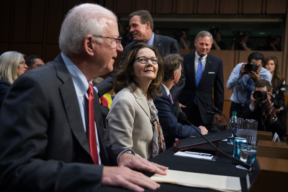 UNITED STATES - MAY 9: Gina Haspel, nominee to be director of the CIA, arrives for her Senate (Select) Intelligence Committee confirmation in Hart Building on May 9, 2018. Seated are former Sens. Saxby Chambliss, R-Ga., left, and Evan Bayh, D-Ind., who introduced her. Standing are Chairman Richard Burr, R-N.C., right, and ranking member Sen. Mark Warner, D-Va. (Photo By Tom Williams/CQ Roll Call)