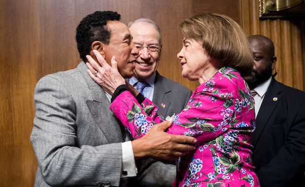 "UNITED STATES - MAY 15: Recording artist Smokey Robinson, left, gives Sen. Dianne Feinstein, D-Calif., a kiss as Sen. Chuck Grassley, R-Iowa, looks on before the start of the Senate Judiciary Committee hearing on ""Protecting and Promoting Music Creation for the 21st Century"" on Tuesday, May 15, 2018. (Photo By Bill Clark/CQ Roll Call)"