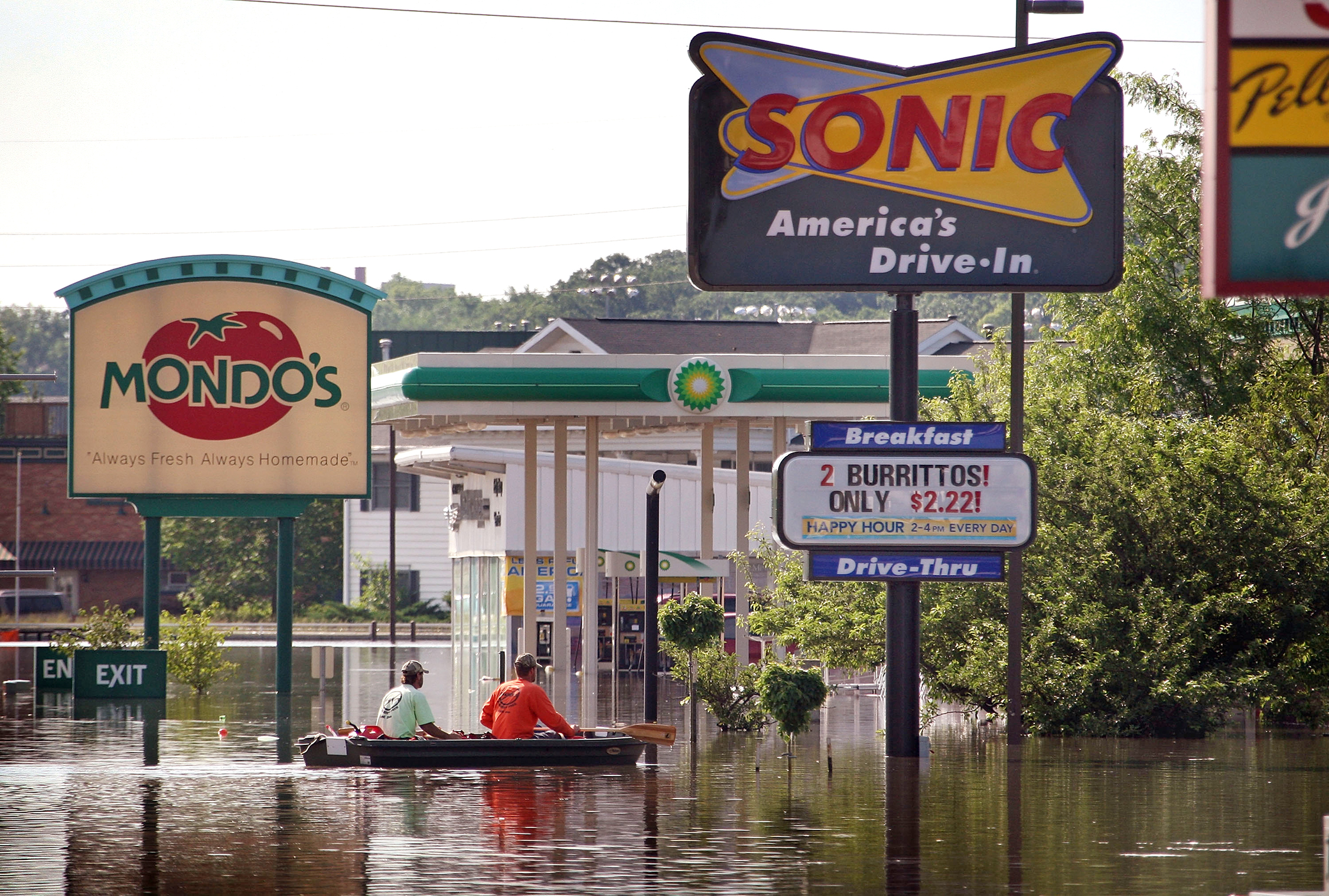 CORALVILLE, IA - JUNE 15: Two men row a boat to thru a flooded area of town known as the strip June 15, 2008 in Coralville, Iowa. The Iowa River is expected to crest in Coralville and Iowa City at record levels Tuesday. (Photo by Scott Olson/Getty Images)