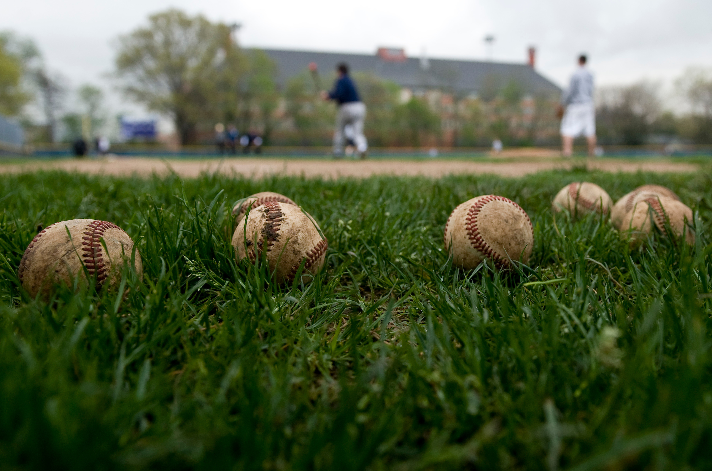 Wet and muddy baseballs sit in the grass as the Democrats baseball team practice in the rain for the Congressional Baseball game at the Hamilton School in NE Washington on Wednesday, April 22, 2009.