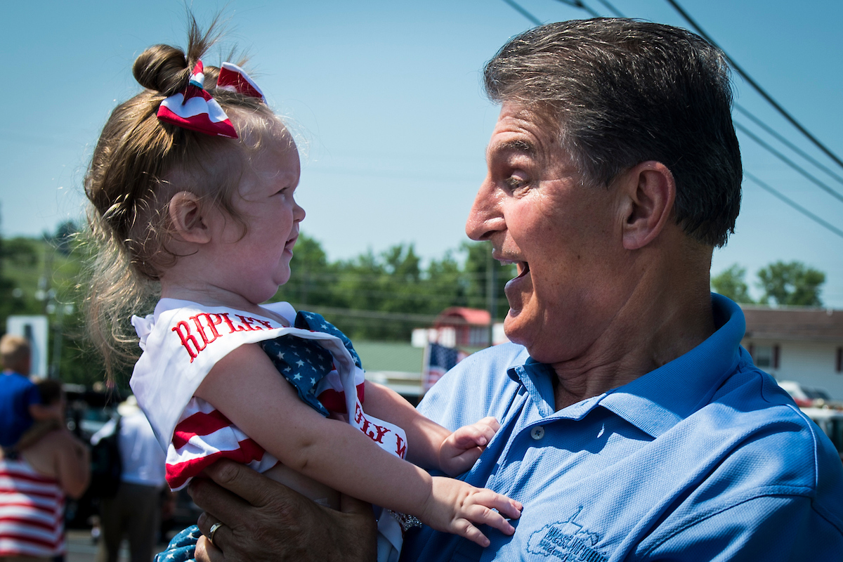 Sen. Joe Manchin III, D-W.Va., holds Ava Lott, this year's Ripley 4th of July Wee Miss, before the start of the July Fourth parade in Ripley, West Virginia, on Wednesday. (Sarah Silbiger/CQ Roll Call)