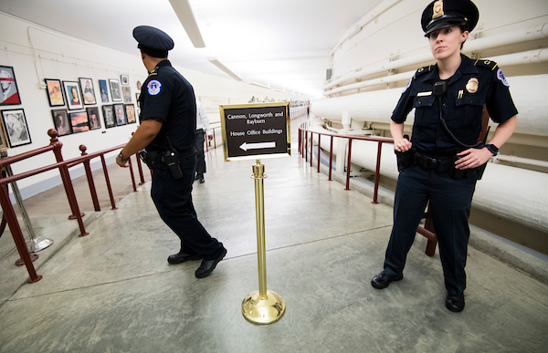 Capitol Police officers keep pedestrians from entering the Cannon Tunnel after heavy rains caused flooding in the walkway from the Capitol to the Cannon House Office Building on Tuesday. (Bill Clark/CQ Roll Call)