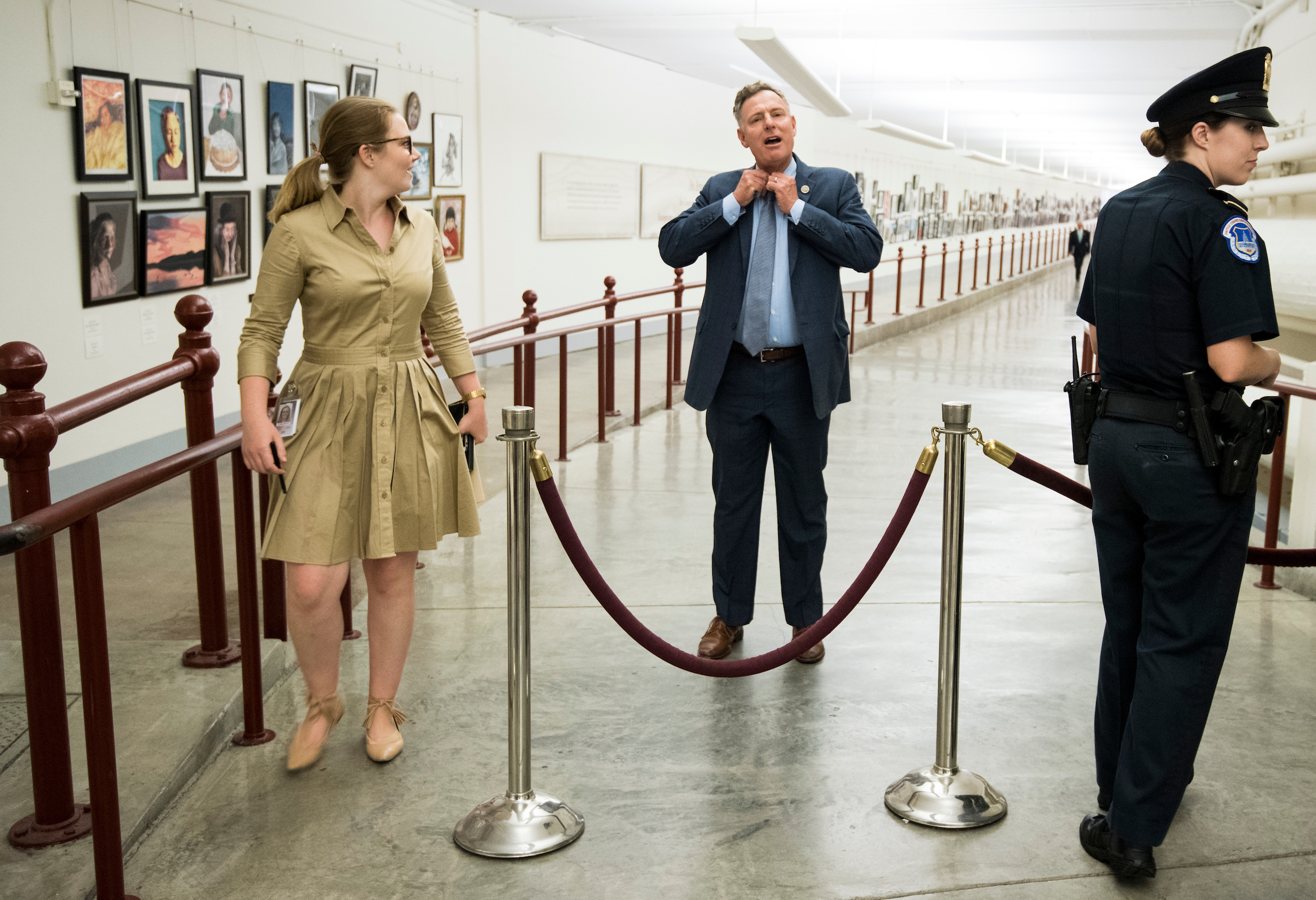 Rep. Scott Peters, D-Calif., fixes his tie as he emerges from the Cannon Tunnel after heavy rains caused Capitol Police to close the walkway due to flooding on Tuesday, July 17, 2018. Capitol Police closed the tunnel (Bill Clark/CQ Roll Call)