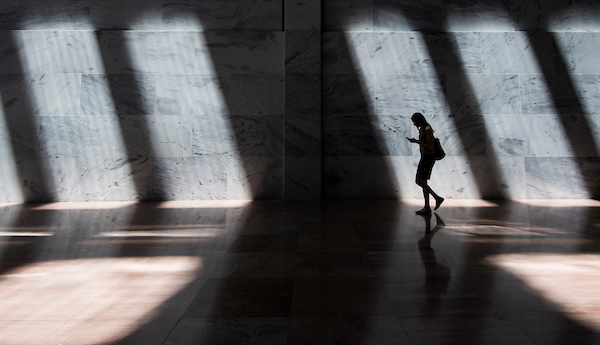 UNITED STATES - JULY 18: A woman walks through the atrium of the Hart Senate Office Building as sun shines through the skylights on Wednesday, July 18, 2018. (Photo By Bill Clark/CQ Roll Call)
