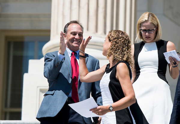 UNITED STATES - JULY 19: From left, Rep. Ed Perlmutter, D-Colo., gets a high five from Rep. Debbie Wasserman Schultz, D-Fla., as they walk down the House steps with Rep. Kyrsten Sinema, D-Ariz., after the final votes of the week on Thursday, July 19, 2018. (Photo By Bill Clark/CQ Roll Call)
