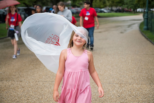 Rowan Toman, 7, from Lakeland, Fla., uses a poncho while walking in the rain toward the East Front of the Capitol July 24, 2018. (Photo By Tom Williams/CQ Roll Call)