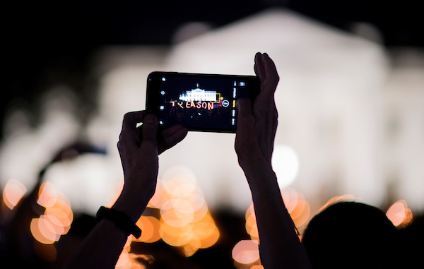 "A protester takes photos of the ""treason"" sign as protesters gather in front of the White House for a rally and candlelight vigil on Wednesday night. The protest was one of 100-Plus events around the country following 12 new indictments in Mueller's Russia Probe and Trump's comments in Helsinki during the summit with Putin. (Bill Clark/CQ Roll Call)"