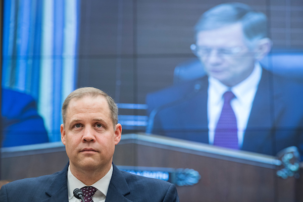 "UNITED STATES - JULY 25: NASA Administrator Jim Bridenstine, left, and Chairman Lamar Smith, R-Texas, on a monitor, are seen during a House Science, Space, and Technology Committee hearing titled ""James Webb Space Telescope: Program Breach and its Implications,"" in Rayburn Building on July 25, 2018. (Photo By Tom Williams/CQ Roll Call)"