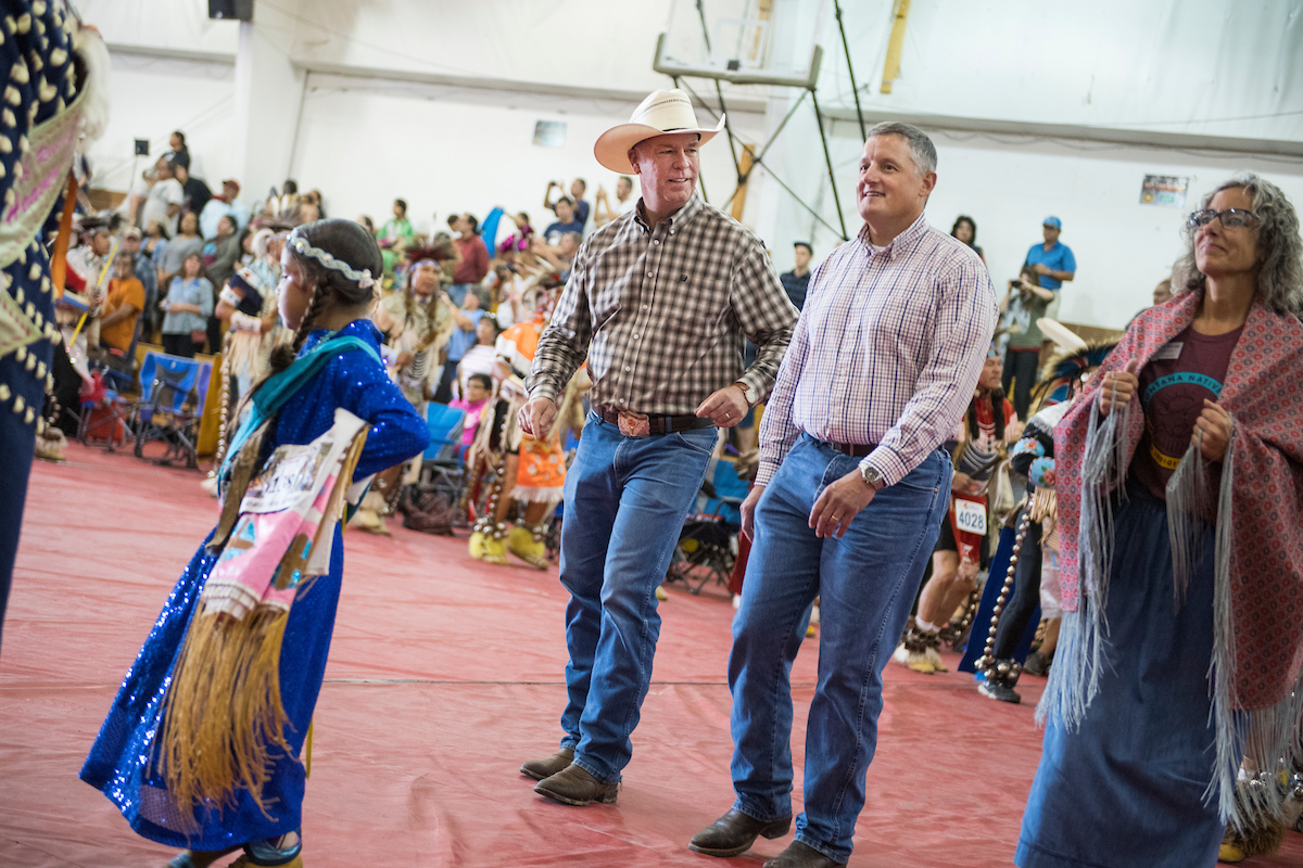 """Don't walk. Dance. Dance."" Those were the orders two weeks ago at Crow Fair in Montana, where GOP Rep. Greg Gianforte, center left, and his Democratic opponent, former state Rep. Kathleen Williams marched in the grand entry together. Arkansas Rep. Bruce Westerman was just along for the ride. (Tom Williams/CQ Roll Call)"