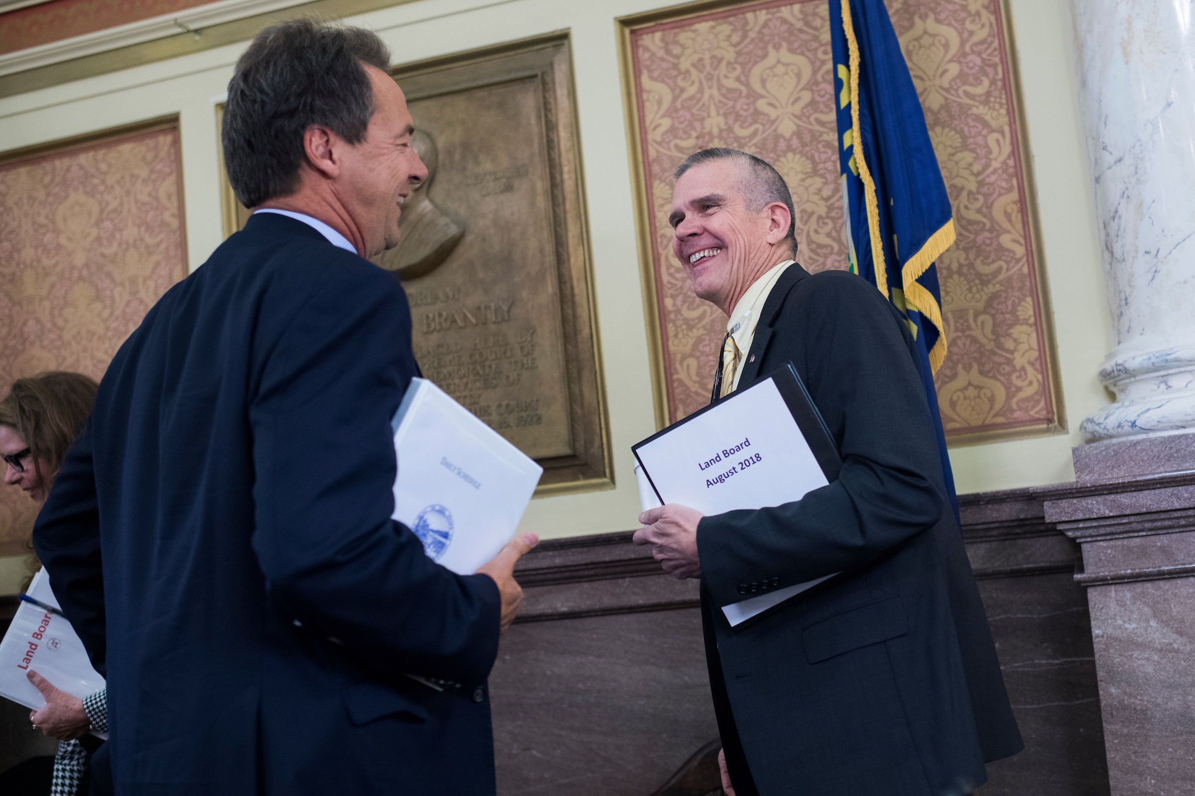 UNITED STATES - AUGUST 20: Matt Rosendale, right, Montana state auditor, talks with Montana Gov. Steve Bullock (D) during a meeting of the Board of Land Commissioners in the State Capitol building in Helena, on August 20, 2018. Rosendale, a Republican, is challenging Sen. Jon Tester, D-Mont., for the senate seat. (Photo By Tom Williams/CQ Roll Call)