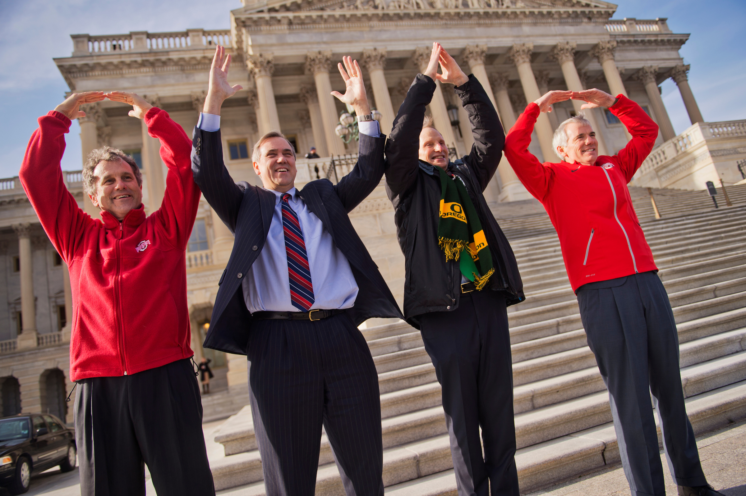 "August isn't usually for politicking. But all eyes are on the Buckeye State this weekend ahead of next week's House special election. From left, Sens. Sherrod Brown, D-Ohio, Jeff Merkley, D-Ore., Ron Wyden, D-Ore., and Rob Portman, R-Ohio, make symbols that spell ""Ohio"" at the Senate steps on Jan. 13, 2015, as part of a football bet. Ohio State beat the University of Oregon 42-20 in the national championship. (Tom Williams/CQ Roll Call file photo)"