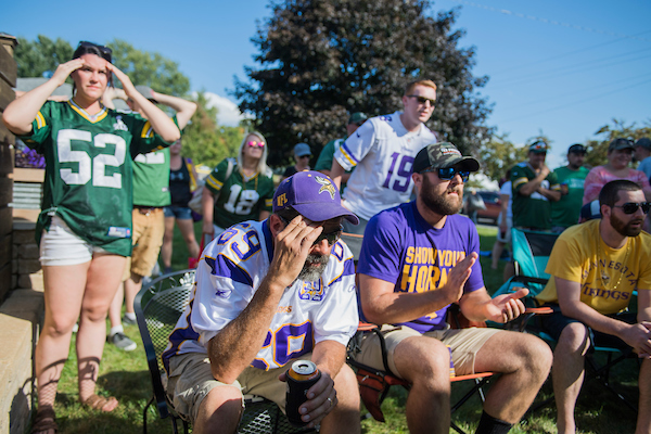 Fans of the Vikings and Packers watch the game, which resulted in a tie, along the Applefest parade route in La Crescent, Minn., on Sunday. Democrat Dan Feehan, and Republican Jim Hagedorn, candidates for Minnesota's 1st Congressional District, walked the parade. (Tom Williams/CQ Roll Call)