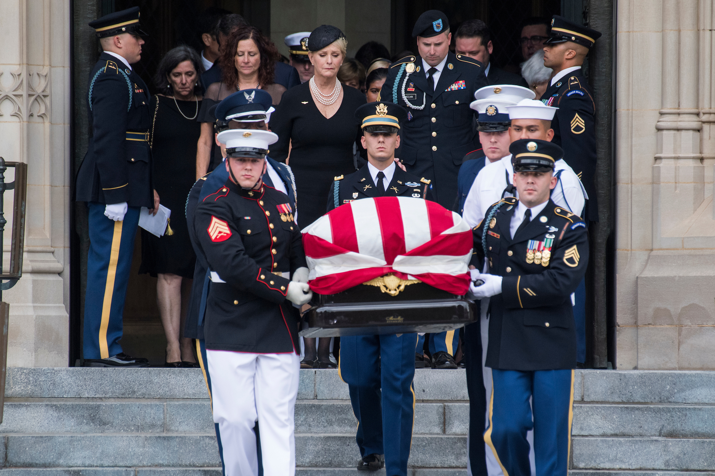 UNITED STATES - SEPTEMBER 1: The casket of late Sen. John McCain, R-Ariz., is carried by an Honor Guard out of the Washington National Cathedral after his funeral on September 1, 2018. His wife, Cindy, and son Jimmy, appear in the background. (Photo By Tom Williams/CQ Roll Call)