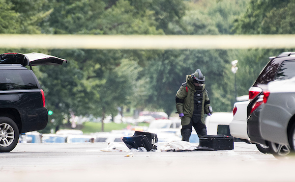 UNITED STATES - SEPTEMBER 12: An officer in a bomb suit sifts through luggage on Louisiana Ave. near the Capitol on Wednesday, Sept. 12, 2018. Capitol Police and other law enforcement were investigating an incident in which a suspect abandoned a suspicious vehicle on Capitol Hill.(Photo By Bill Clark/CQ Roll Call)