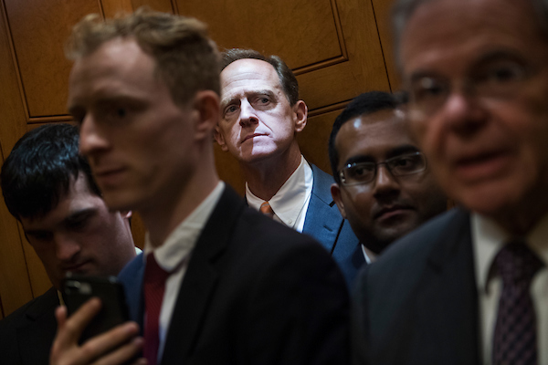 UNITED STATES - SEPTEMBER 25: Sens. Pat Toomey, R-Pa., background, and Bob Menendez, D-N.J., are seen in the Capitol before the Senate policy luncheons on September 25, 2018. (Photo By Tom Williams/CQ Roll Call)