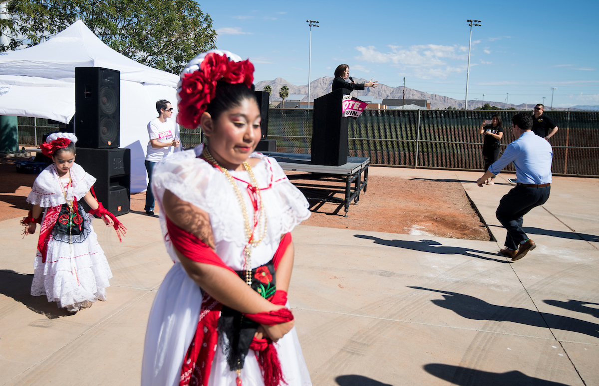 Sen. Catherine Cortez Masto, D-Nev., speaks on stage as dancers with the Mexico Vivo group prepare to perform at the East Las Vegas Community Center. (Bill Clark/CQ Roll Call)