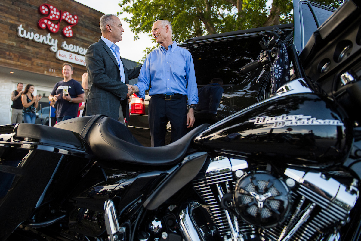 UNITED STATES - NOVEMBER 4: Florida Gov. Rick Scott (R), right, who is running for the U.S. Senate, talks with Andrew Pollack, whose daughter, Meadow, was killed in the Parkland school shooting, during a rally hosted by Bikers for Trump at the 27 Bar & Lounge in Fort Lauderdale on November 4, 2018. (Photo By Tom Williams/CQ Roll Call)