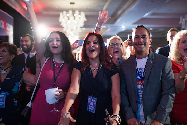 Yvette Benarroch, center, and guests of an election night party for GOP Florida Senate candidate and current Gov. Rick Scott cheer as they watch returns at LaPlaya resort in Naples, Fla. (Tom Williams/CQ Roll Call)