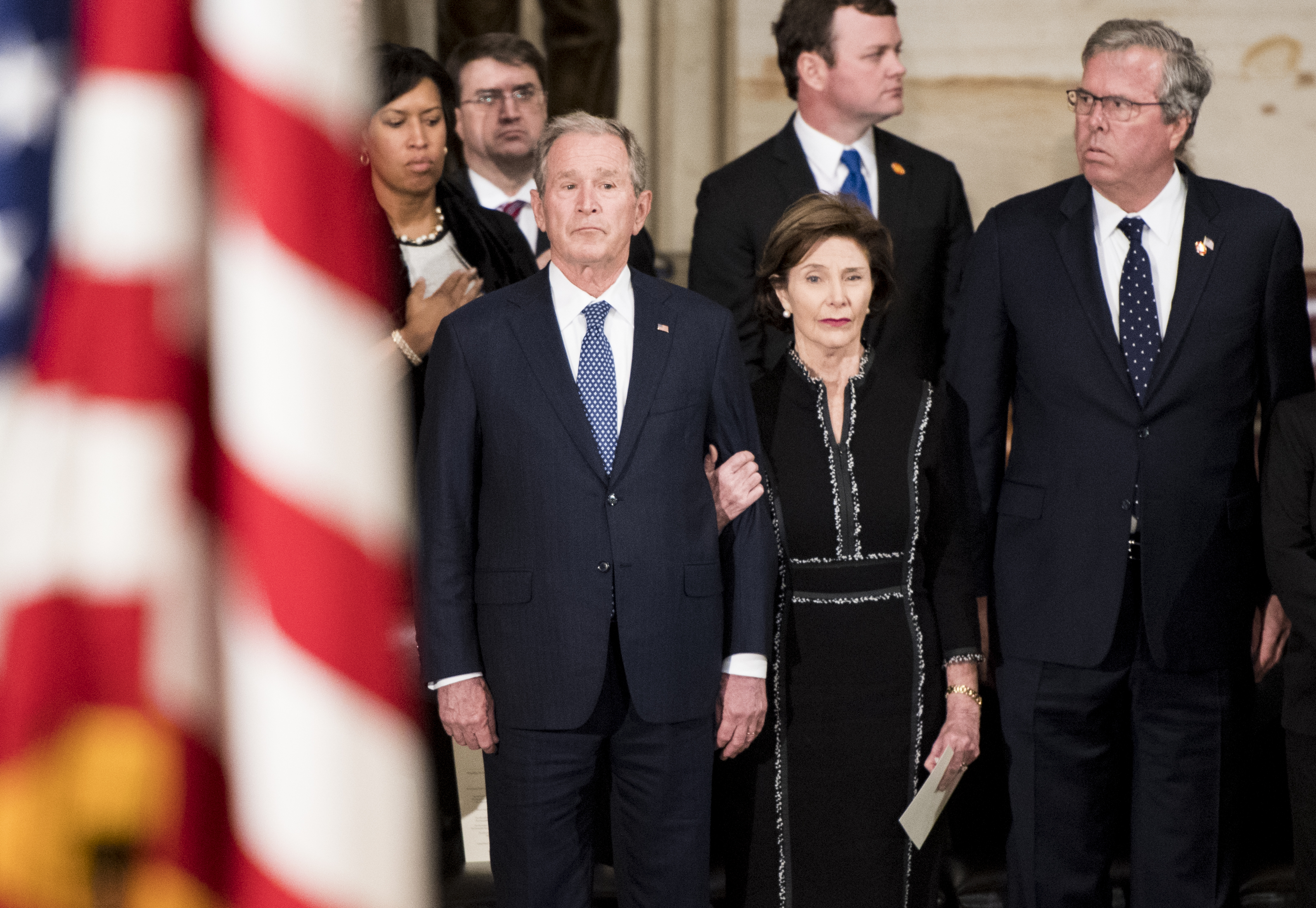 UNITED STATES - DECEMBER 3: From left, former President George W. Bush, former first lady Laura Bush, and former Gov. Jeb Bush watch as former President George H.W. Bush's casket is carried into the Capitol Rotunda on Monday, Dec. 3, 2018, where he will lay in state until Wednesday. (Photo By Bill Clark/CQ Roll Call)