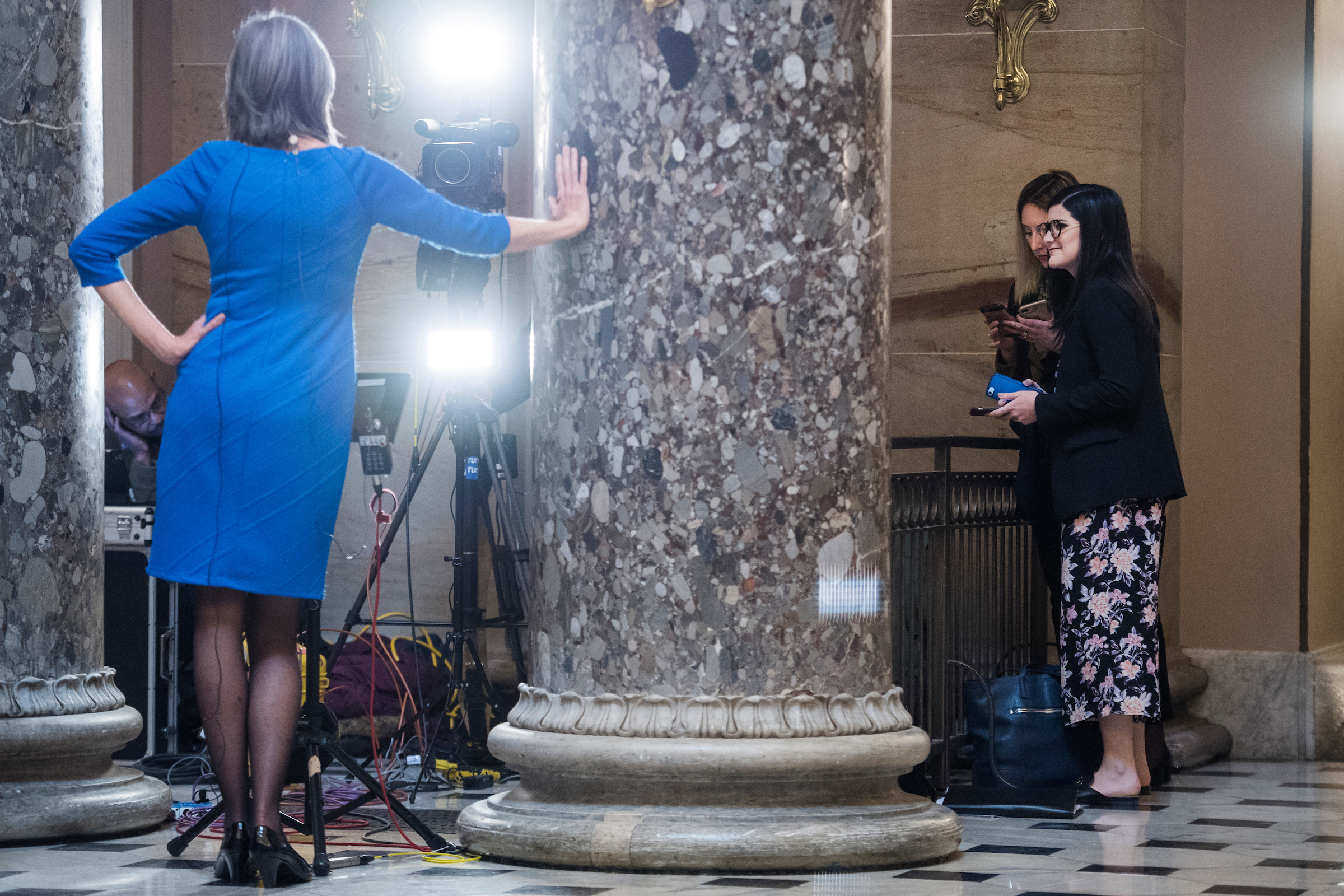 Rep. Katherine Clark, D-Mass., left, vice chair of the House Democratic Caucus, and her aides, wait to conduct a television interview in the Capitol's Statuary Hall on Wednesday, Jan. 23, 2019. (Tom Williams/CQ Roll Call)