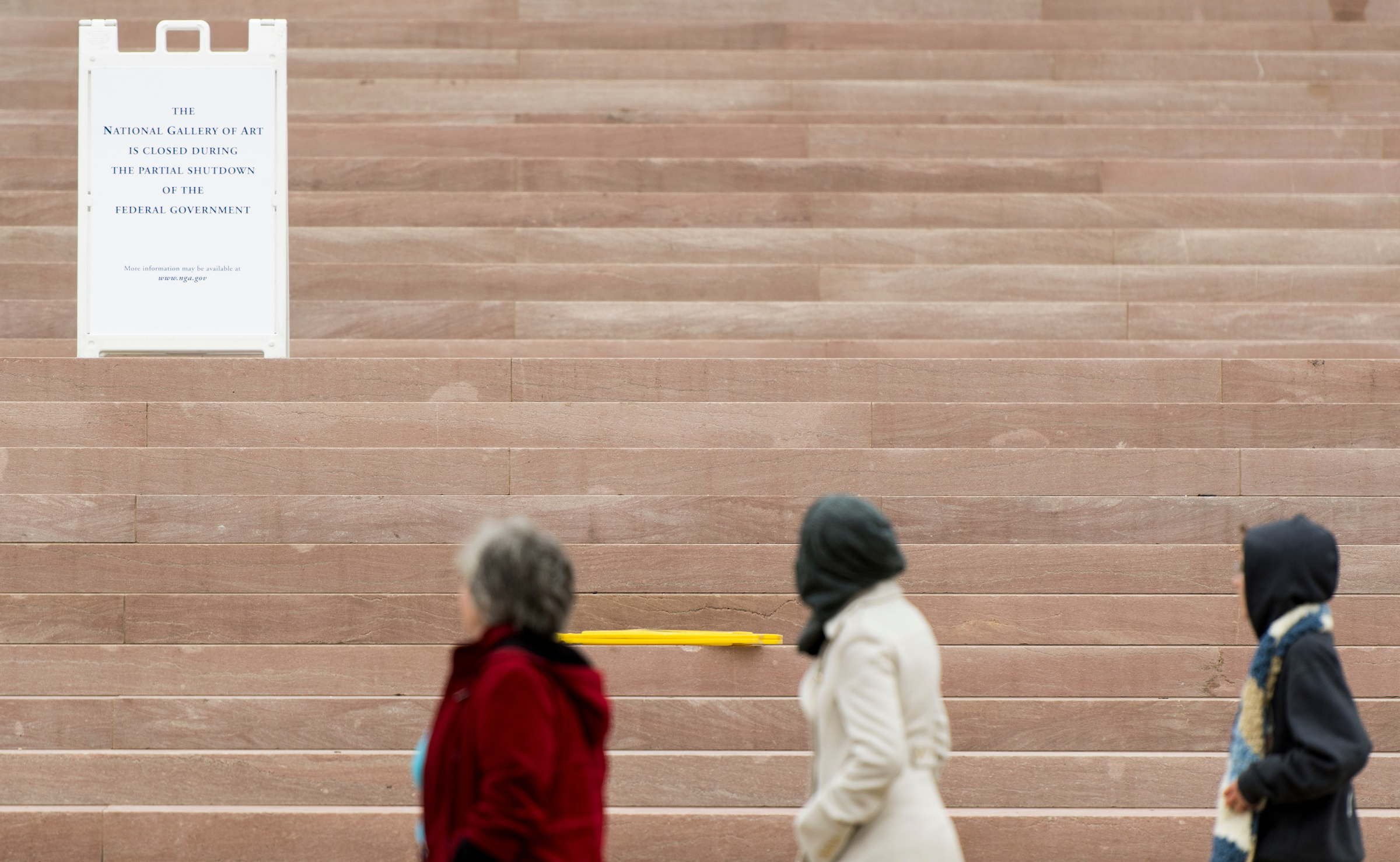 UNITED STATES - JANUARY 7: Tourists walk past a sign announces that the National Gallery of Art is closed due to the partial government shut down on Monday, Jan. 7, 2019. The standoff between President Trump and Congress over a spending package to fund nine government agencies reached its 17th day Monday, making this shut down the third-longest on record. (Photo By Bill Clark/CQ Roll Call)
