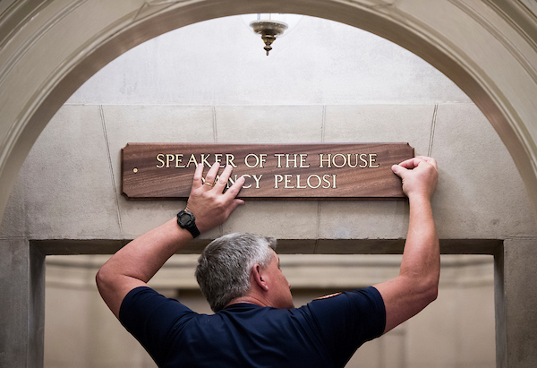 Architect of the Capitol employee Gary Bullis hangs the new sign at the entran ce to Speaker of the House Nancy Pelosi's office suite after she was elected Speaker on Thursday, Jan. 3, 2019. (Bill Clark/CQ Roll Call)