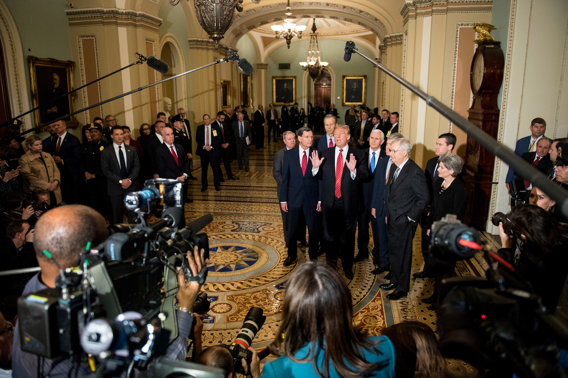 UNITED STATES - JANUARY 9: President Donald Trump, flanked from left by Sen. Lindsey Graham, R-S.C., Sen. John Barrasso, R-Wyo., Sen. John Thune, R-S. Dak., Vice President Mike Pence, Sen. Roy Blunt, R-Mo., Senate Majority Leader Mitch McConnell, R-Ky., Sen. Todd Young, R-Ind., and Sen. Joni Ernst, R-Iowa, stops to speak to the cameras following his lunch with Senate Republicans in the Capitol on Wed. Jan. 9, 2018. (Photo By Bill Clark/CQ Roll Call)