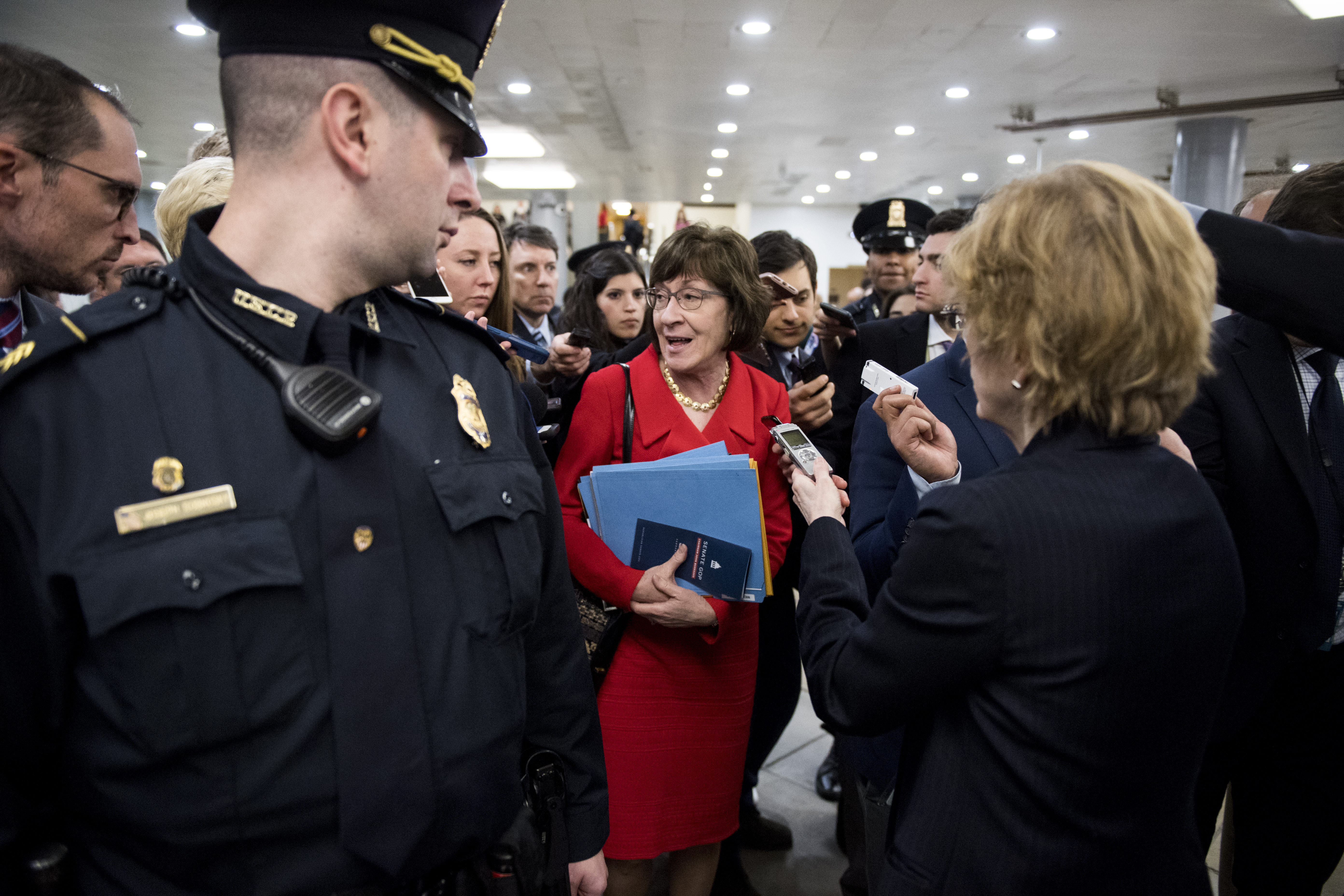 UNITED STATES - FEBRUARY 14: Capitol Police escort Sen. Susan Collins, R-Maine, through reporters to the Senate Subway following the vote to keep the government open on Feb. 14, 2019. (Photo By Bill Clark/CQ Roll Call)