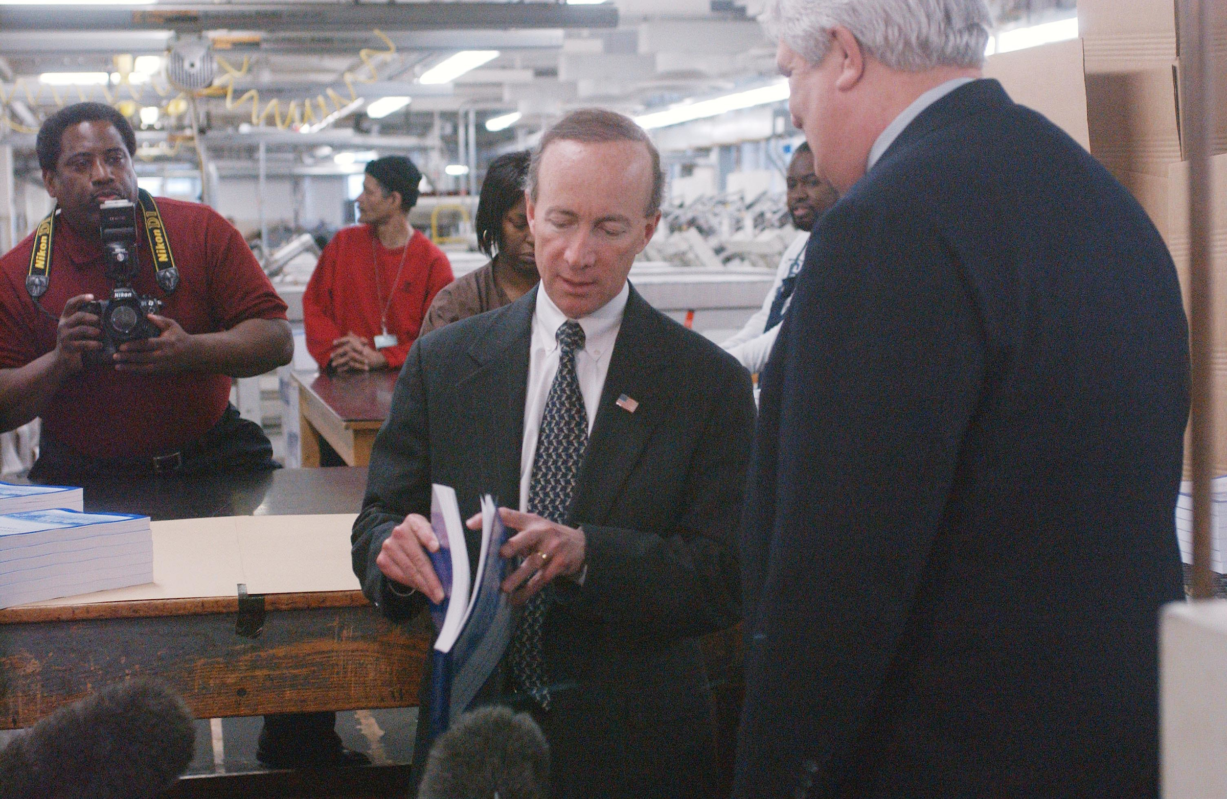 Office of Management and Budget Director Mitchell E. Daniels Jr., and Public Printer of the United States Bruce R. James during a photo opp as copies of the Bush administration's Fiscal 2004 federal budget come off the binder at the U.S. Government Printing Office in Washington, D.C. (Scott Ferrell/CQ Roll Call file photo.)