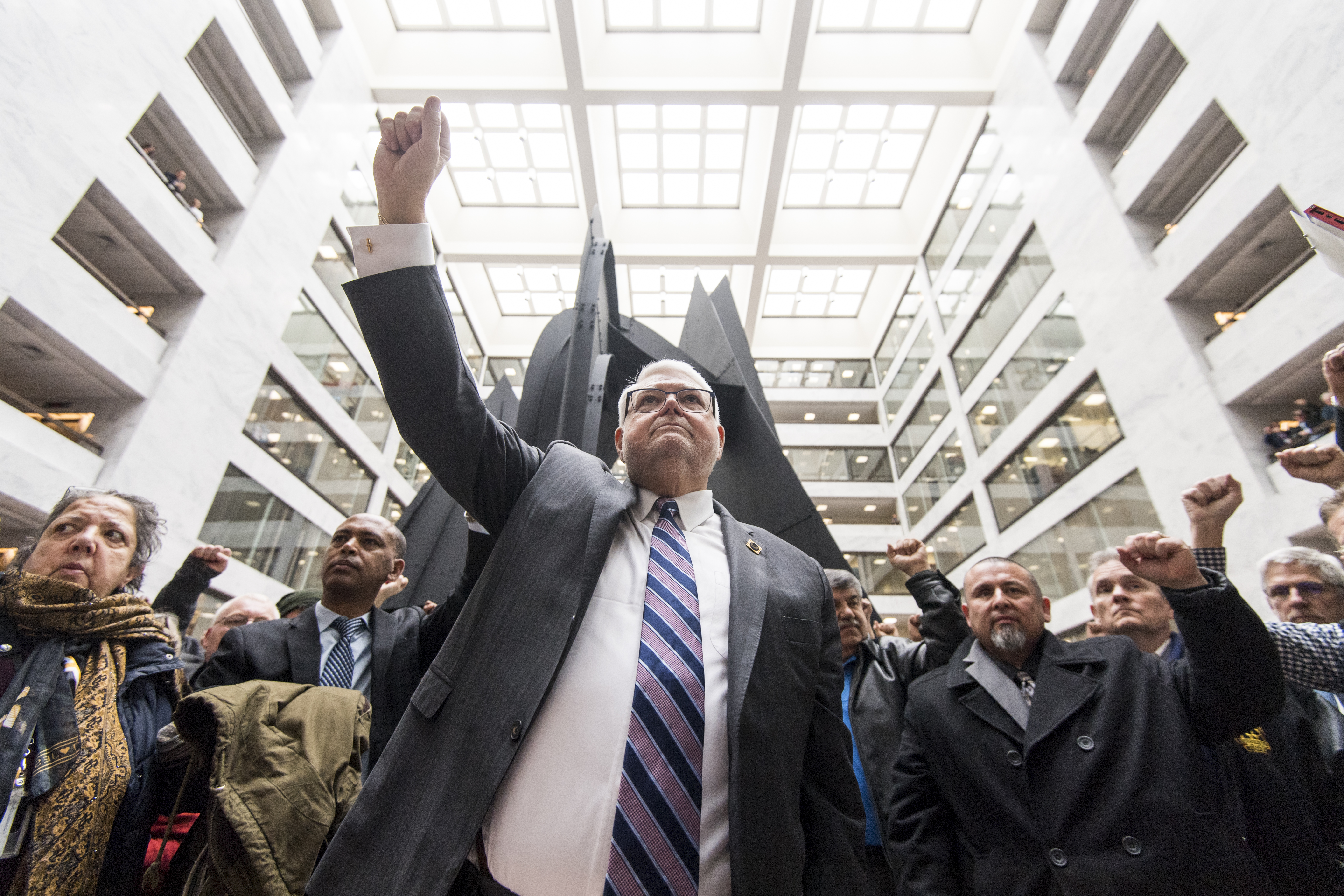 UNITED STATES - FEBRUARY 13: J. David Cox Sr., president of the American Federation of Government Employees, holds up his fist as federal workers hold a sildent protest for 35 minutes in the Hart Senate Office Building to call on law makers and President Trump to keep the government open on Wednesday, Feb. 13, 2019. (Photo By Bill Clark/CQ Roll Call)