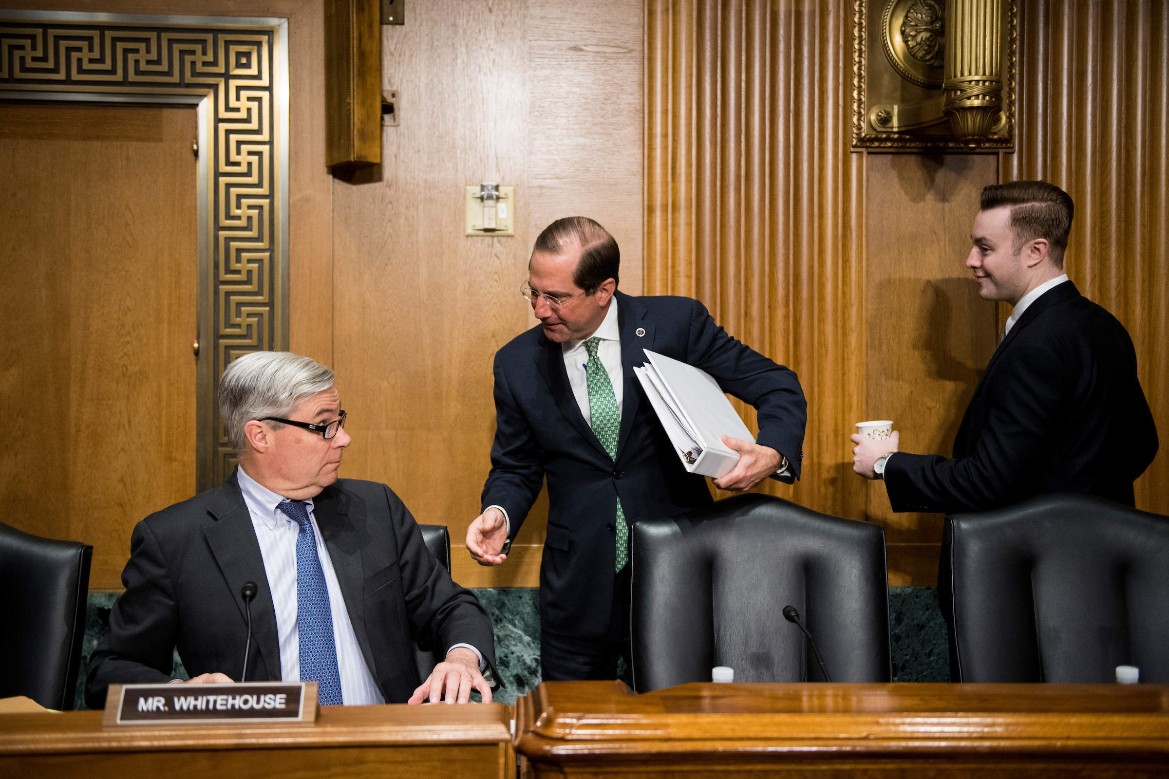 "Secretary of Health and Human Services Alex Azar, center, speaks with Sen. Sheldon Whitehouse, D-R.I., before the start of the Senate Finance Committee hearing on ""The President's FY2020 Budget"" on Thursday, March 14, 2019. (Photo By Bill Clark/CQ Roll Call)"