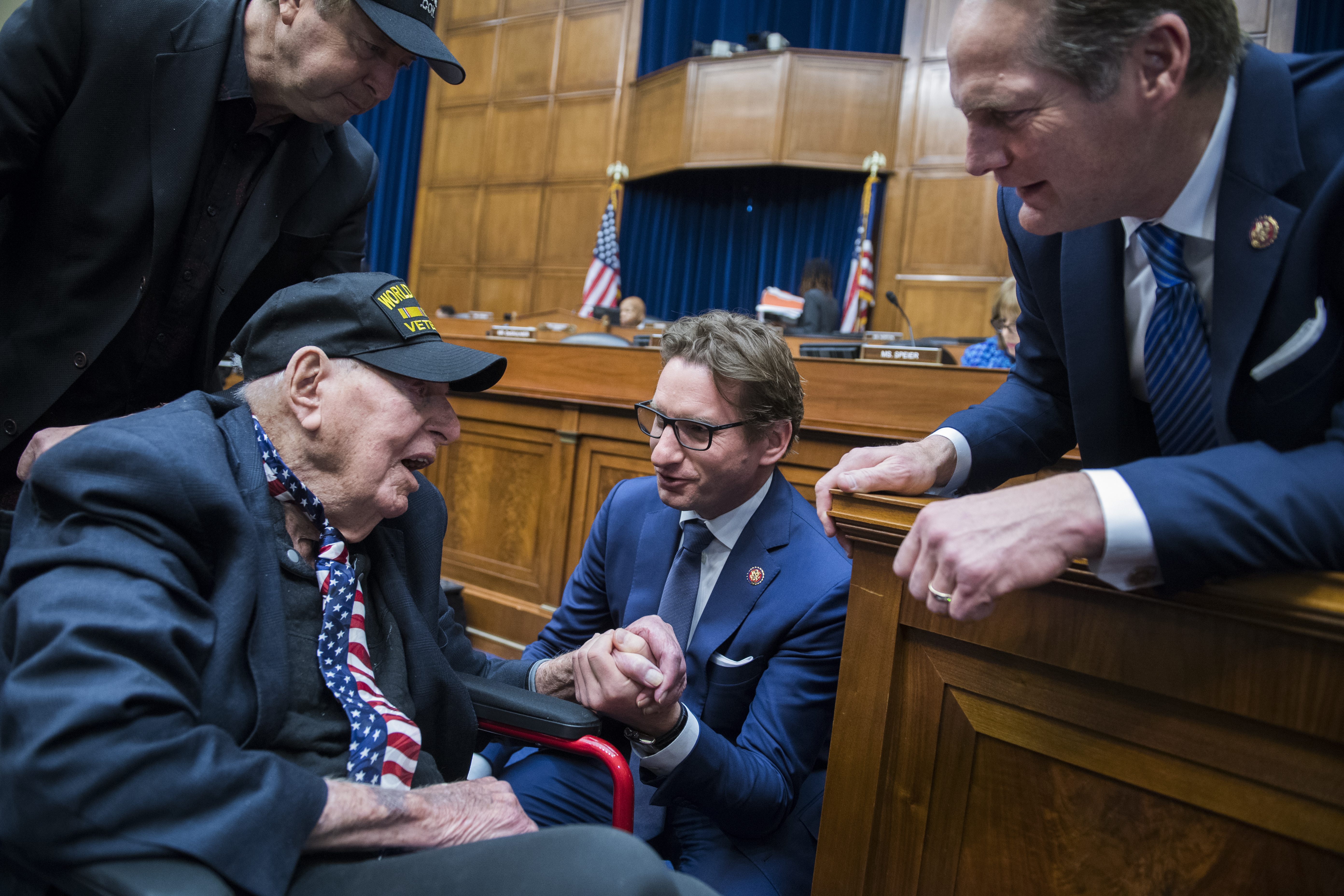 UNITED STATES - FEBRUARY 27: Reps. Dean Phillips, D-Minn., center, and Harley Rouda, D-Calif., right, talks with World War II veteran Sidney Walton, 100, of San Diego, during a break in a House Oversight and Reform Committee hearing in Rayburn Building featuring testimony by Michael Cohen, former attorney for President Donald Trump, on Russian interference in the 2016 election on Wednesday, February 27, 2019. Walton, seen with his son Paul, left, served in India during the war. (Photo By Tom Williams/CQ Roll Call)