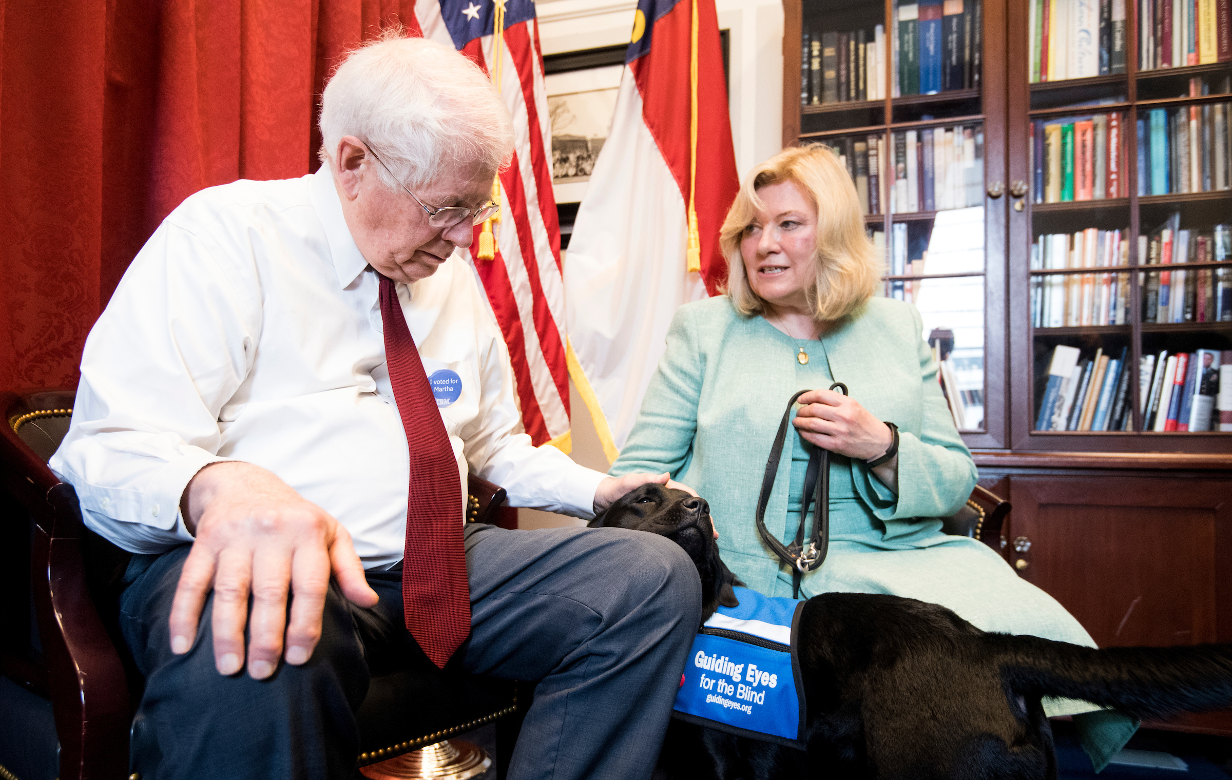 "UNITED STATES - MAY 1: Volunteer puppy raiser Lorraine Trapani speaks with Rep. David Price, D-N.C., as he pets Kate, a 14 month old black labrador retriever in the Guiding Eyes for the Blind training program, in his office on Wednesday, May 1, 2019. Kate is wearing a ""smart collar"" using IBM technology to help evaluate which dogs are best suited for the program. (Photo By Bill Clark/CQ Roll Call)"