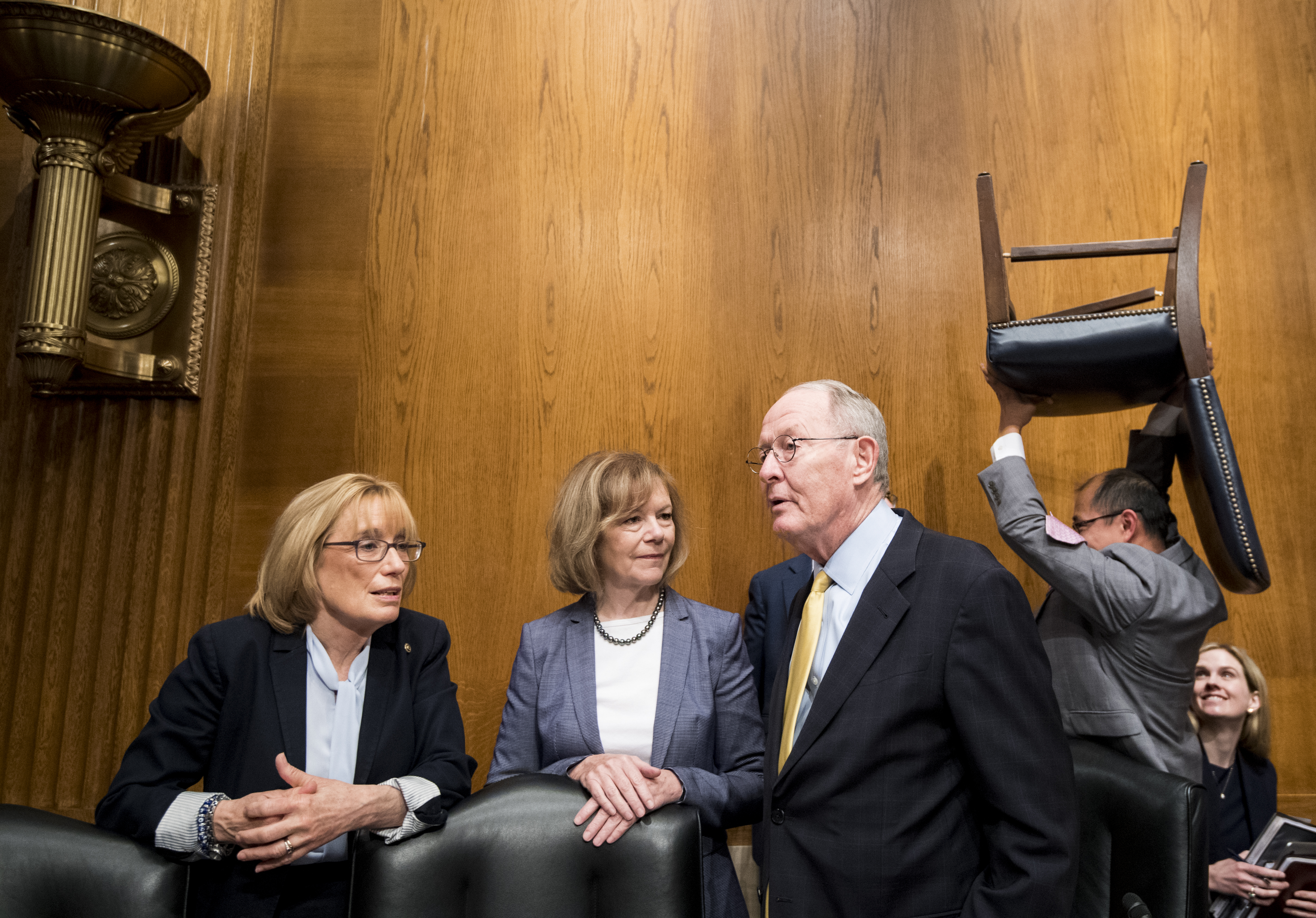 """UNITED STATES - JUNE 18: From left, Sen. Maggie Hassan, D-N.H., Sen. Tina Smith, D-Minn., and chairman Sen. Lamar Alexander, R-Tenn., talk as a staffer carries a chair behind them before the start of the Senate Health, Education, Labor and Pensions Committee hearing on the """"Lower Health Care Costs Act of 2019""""on Tuesday, June 18, 2019. (Photo By Bill Clark/CQ Roll Call)"""