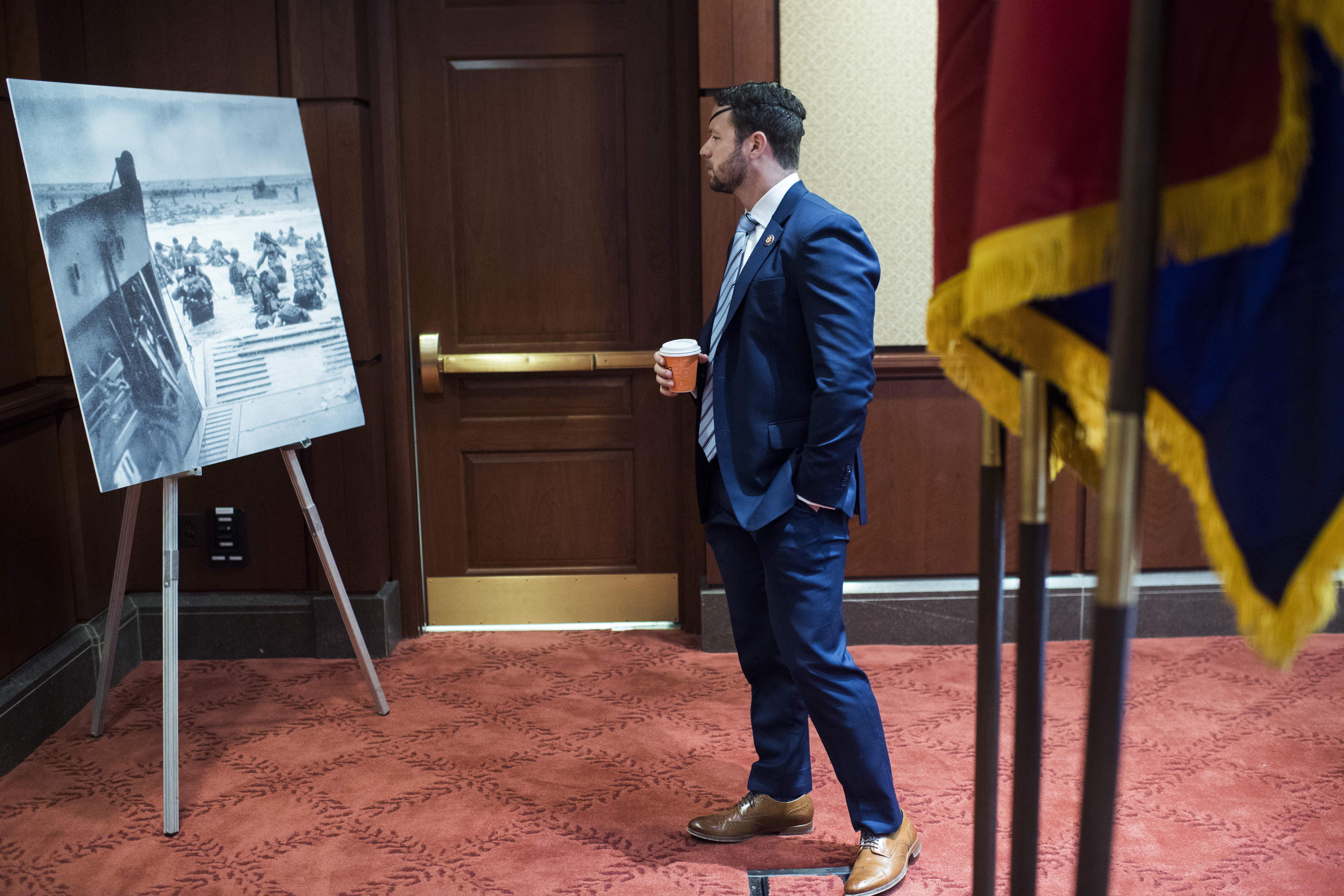 UNITED STATES - JUNE 4: Rep. Dan Crenshaw, R-Texas, looks at a picture of the Normandy landings during an event with the U.S. Holocaust Memorial Museum to honor the 75th anniversary of D-Day in the Capitol Visitor Center on Tuesday, June 4, 2019. (Photo By Tom Williams/CQ Roll Call)