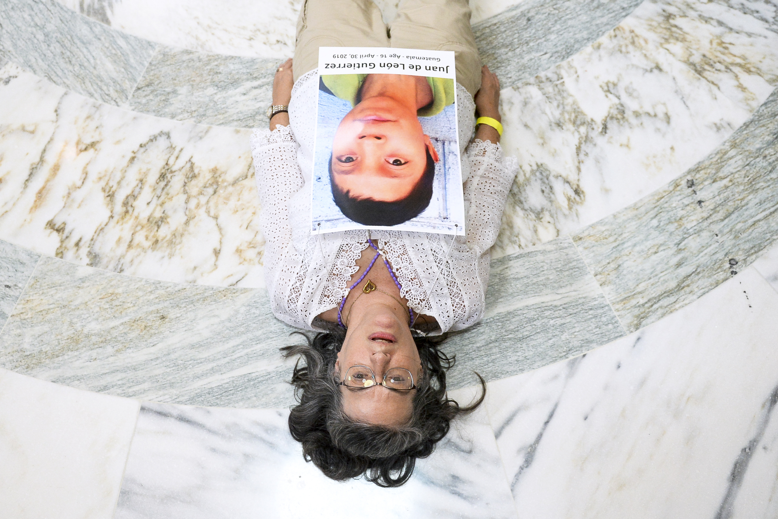 UNITED STATES - JULY 18: A woman a part of a coalition of Catholic activists lays on the ground as she protests to pressure the Trump administration and Congress to end the practice of detaining immigrant children in the Russell Rotunda at the Capitol on Thursday July 18, 2019. (Photo by Caroline Brehman/CQ Roll Call)