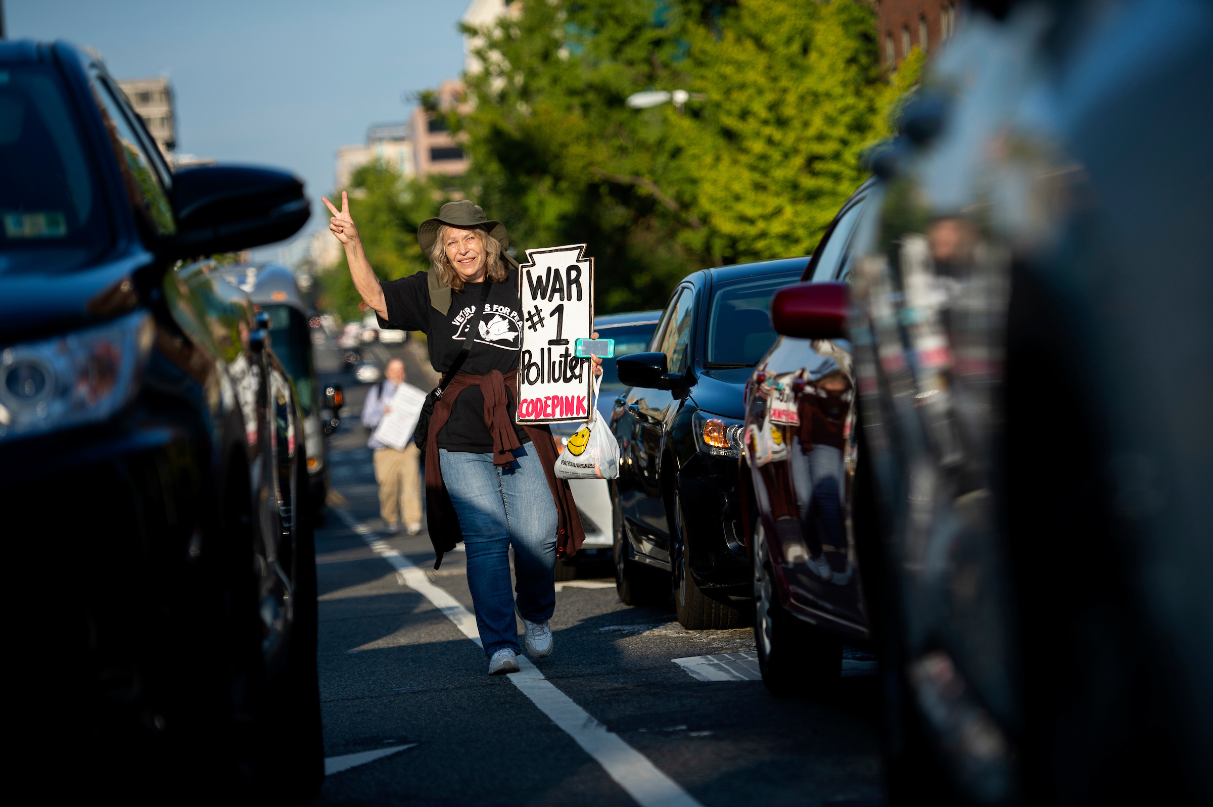 "UNITED STATES - SEPTEMBER 23: A climate change protester walks through morning traffic near the U.S. Capitol at rush hour on Monday, Sept. 23, 2019. A coalition of climate activists under the umbrella ""Shut Down D.C."" blocked intersections throughout DC to draw attention to climate change. (Photo by Caroline Brehman/CQ Roll Call)"