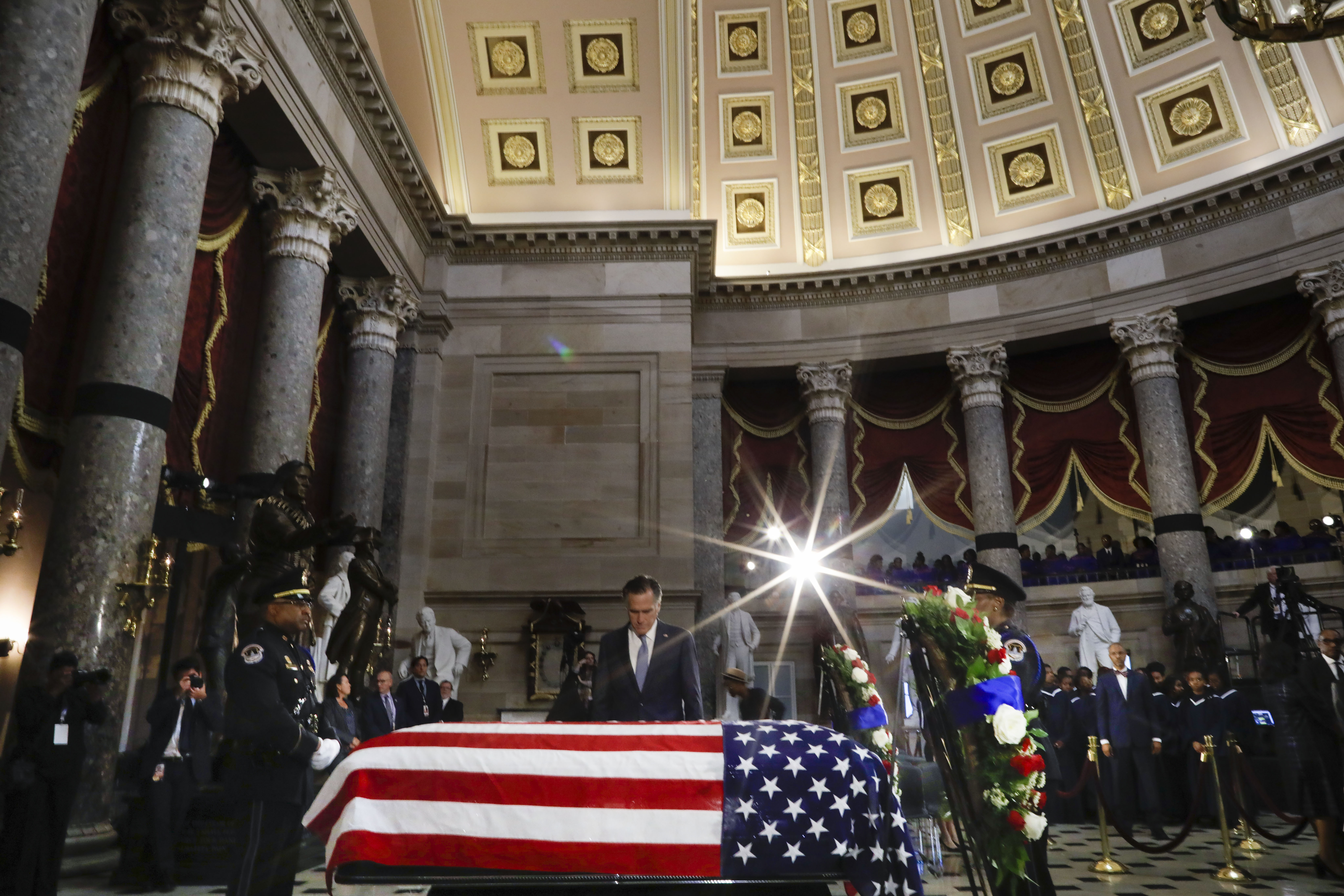 "WASHINGTON, DC - OCTOBER 24: U.S. Sen. Mitt Romney (R-UT) stops to pay his respects over the flag-draped casket of U.S. Rep. Elijah Cummings (D-MD) in National Statuary Hall at the U.S. Capitol during a memorial service October 24, 2019 in Washington, DC. Rep. Cummings passed away on October 17, 2019 at the age of 68 from ""complications concerning longstanding health challenges."" (Photo by Pablo Martinez Monsivais-Pool/Getty Images)"