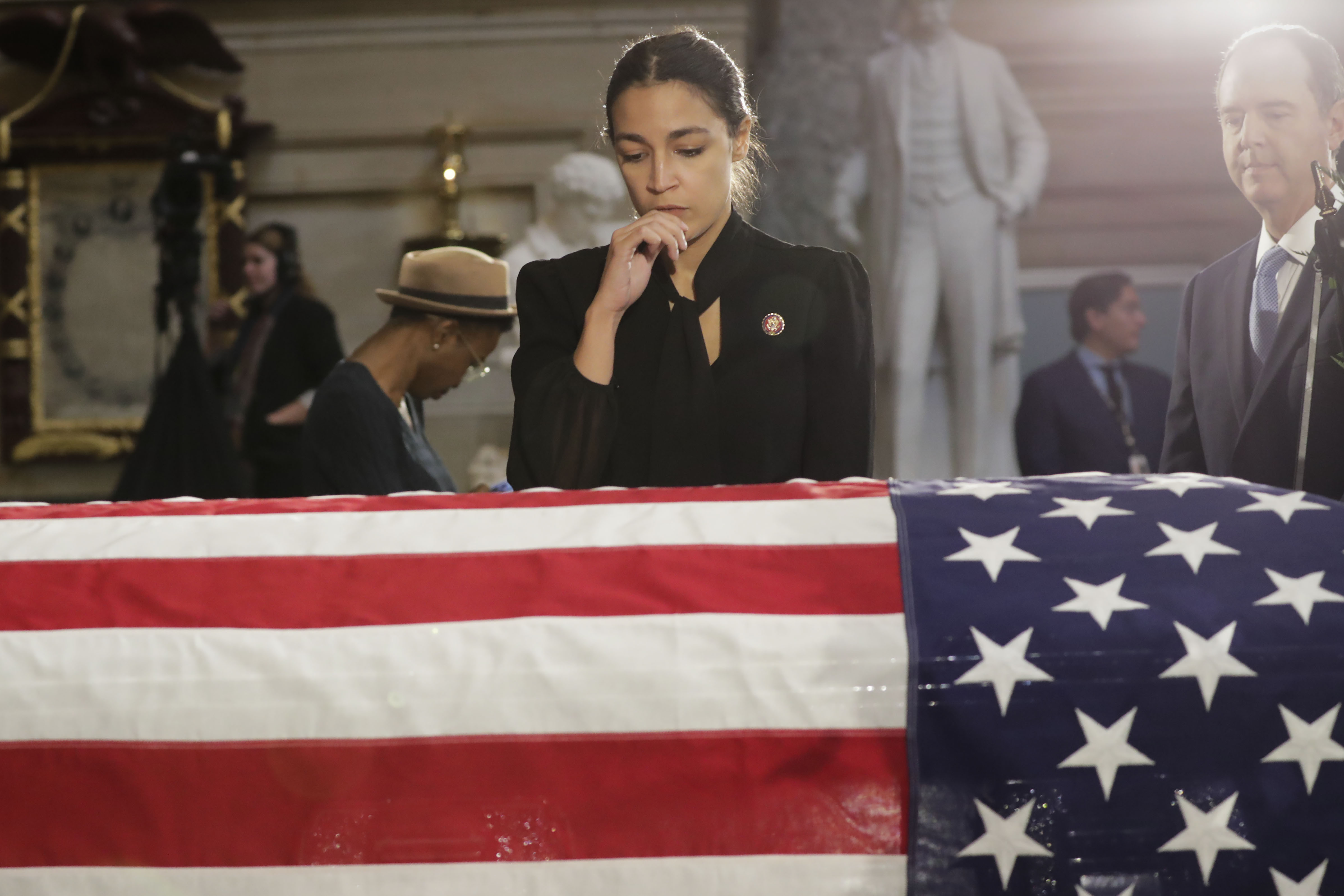 "WASHINGTON, DC - OCTOBER 24: U.S. Rep. Alexandria Ocasio-Cortez (D-NY) stops to pay her respects over the flag-draped casket of U.S. Rep. Elijah Cummings (D-MD) in National Statuary Hall at the U.S. Capitol during a memorial service October 24, 2019 in Washington, DC. Rep. Cummings passed away on October 17, 2019 at the age of 68 from ""complications concerning longstanding health challenges."" (Photo by Pablo Martinez Monsivais-Pool/Getty Images)"