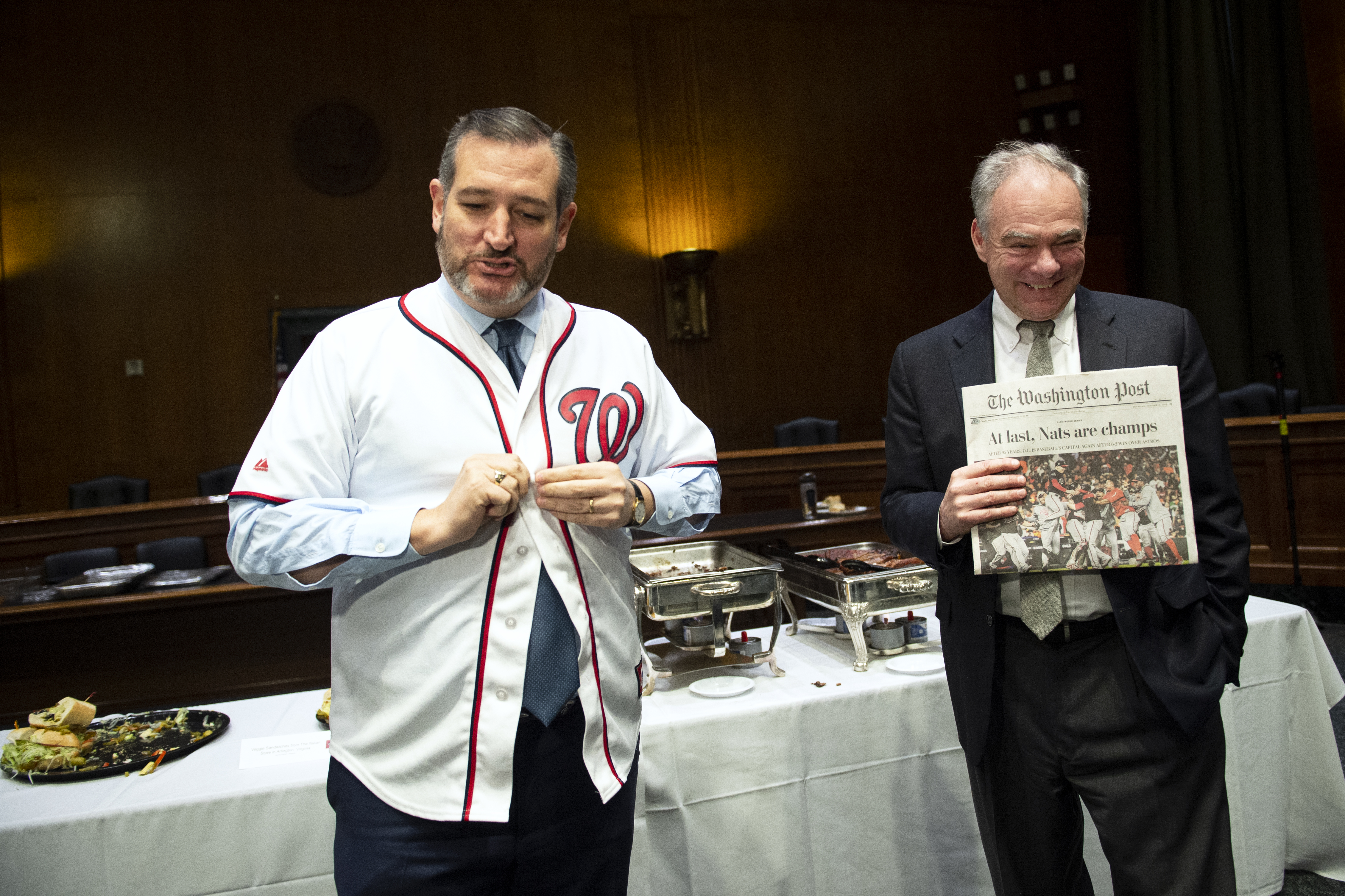 UNITED STATES - DECEMBER 5: Sen. Ted Cruz, R-Texas, left, puts on a Washington Nationals jersey after losing a World Series bet to Sen. Tim Kaine, D-Va., in the Capitol on Thursday Dec. 5, 2019. As the loser, Sen. Ted Cruz, R-Texas, provided a Texas themed buffet for his and Kaine's staffers. (Photo by Caroline Brehman/CQ Roll Call)