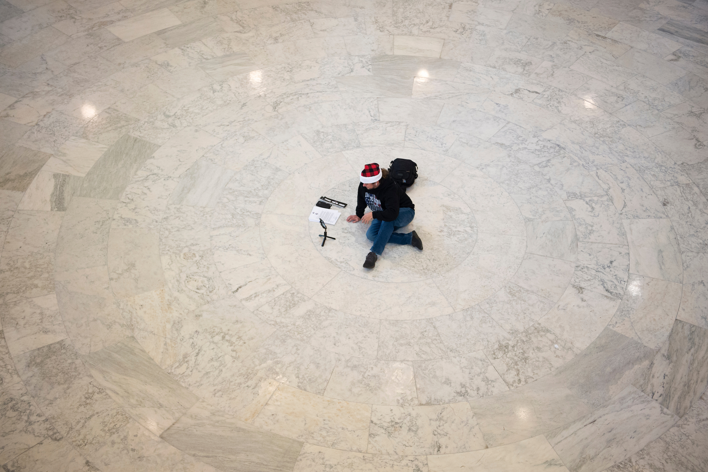 A pro-impeachment demonstrator records a video on a smartphone in the Cannon rotunda on Wednesday. (Caroline Brehman/CQ Roll Call)