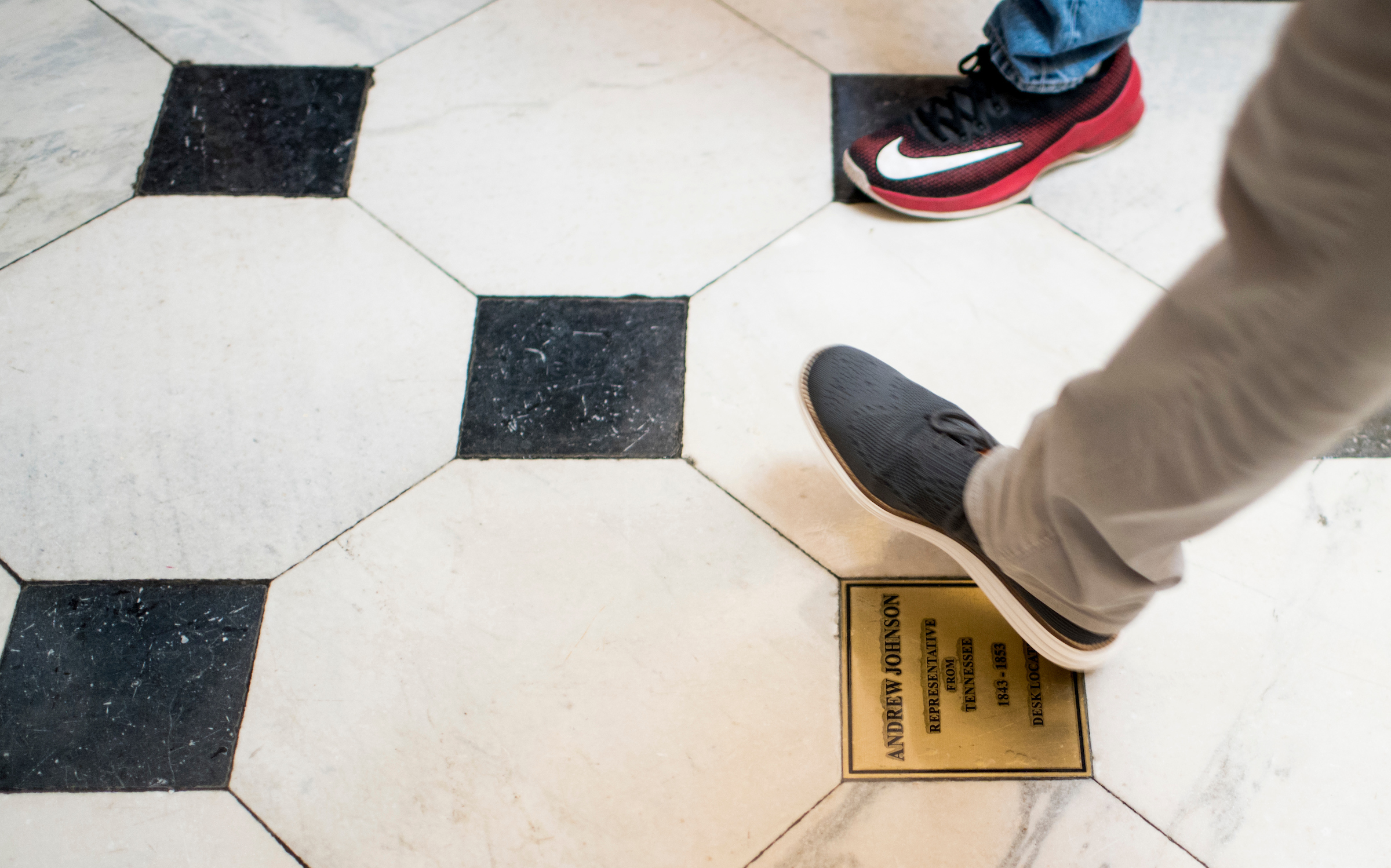 Tourists on Wednesday walk past a plaque in Statuary Hall marking Andrew Johnson's congressional seat. Johnson became the first U.S. president to be impeached, in 1868. (Bill Clark/CQ Roll Call)