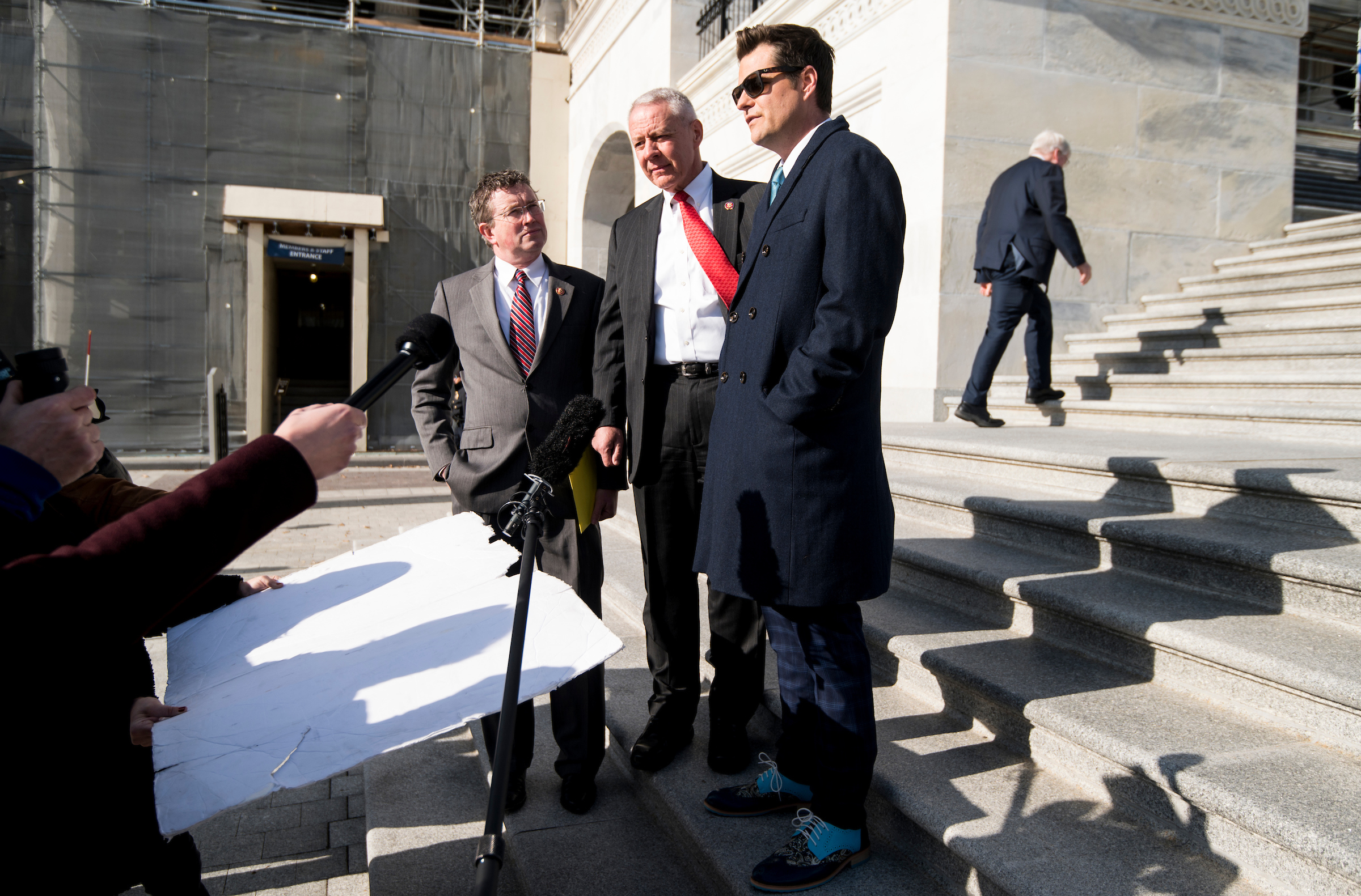 From left, Reps. Thomas Massie, R-Ky., Ken Buck, R-Colo., and Matt Gaetz, R-Fla., stop on the House steps to speak to a film crew as they arrive to vote on the impeachment rules package. (Bill Clark/CQ Roll Call)