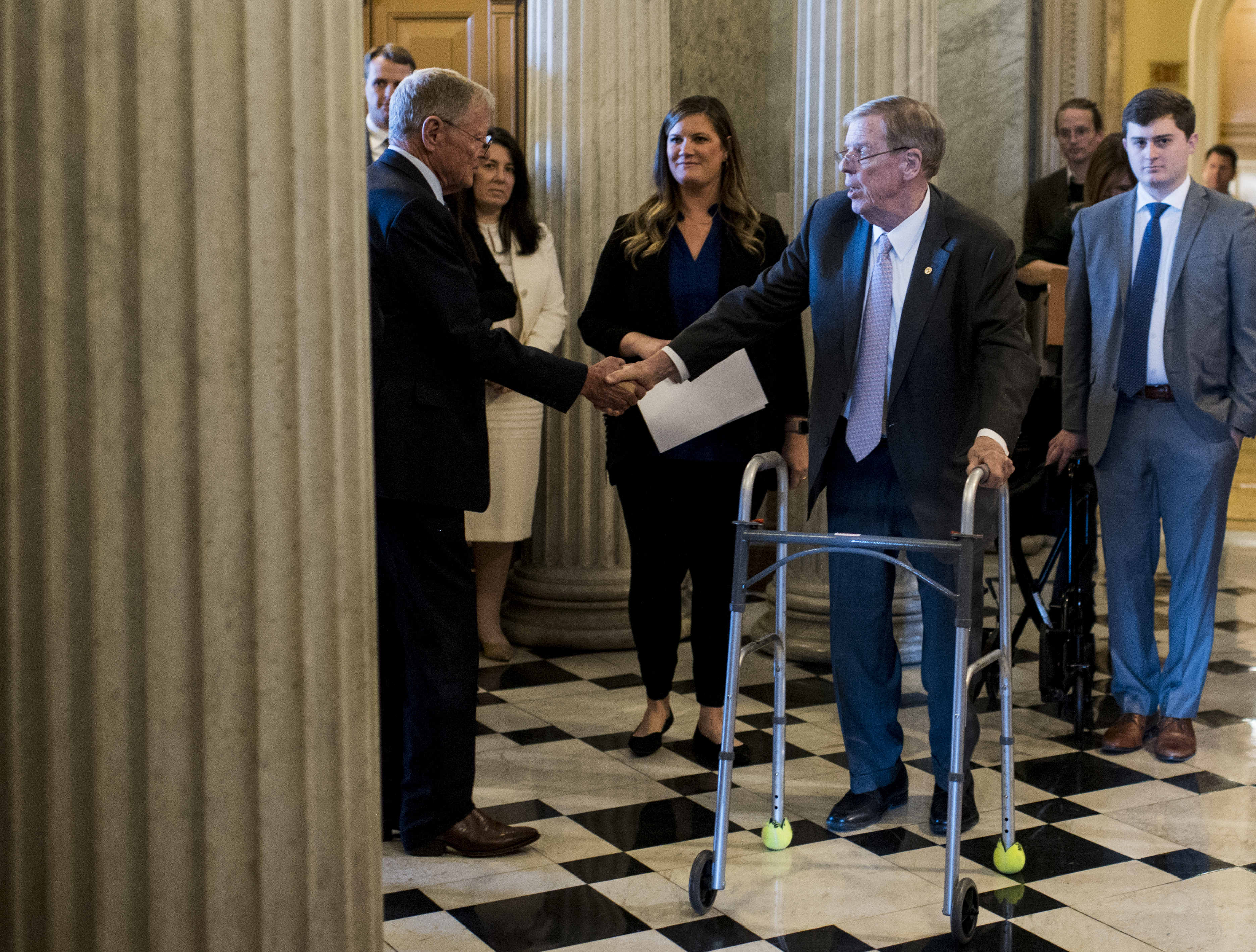 UNITED STATES - DECEMBER 3: Sen. Johnny Isakson, R-Ga., right, shakes hands with Sen. Jim Inhofe, R-Okla., as he walks to the Senate floor to deliver his farewell address in the Capitol on Tuesday, Dec. 3, 2019. (Photo By Bill Clark/CQ Roll Call)