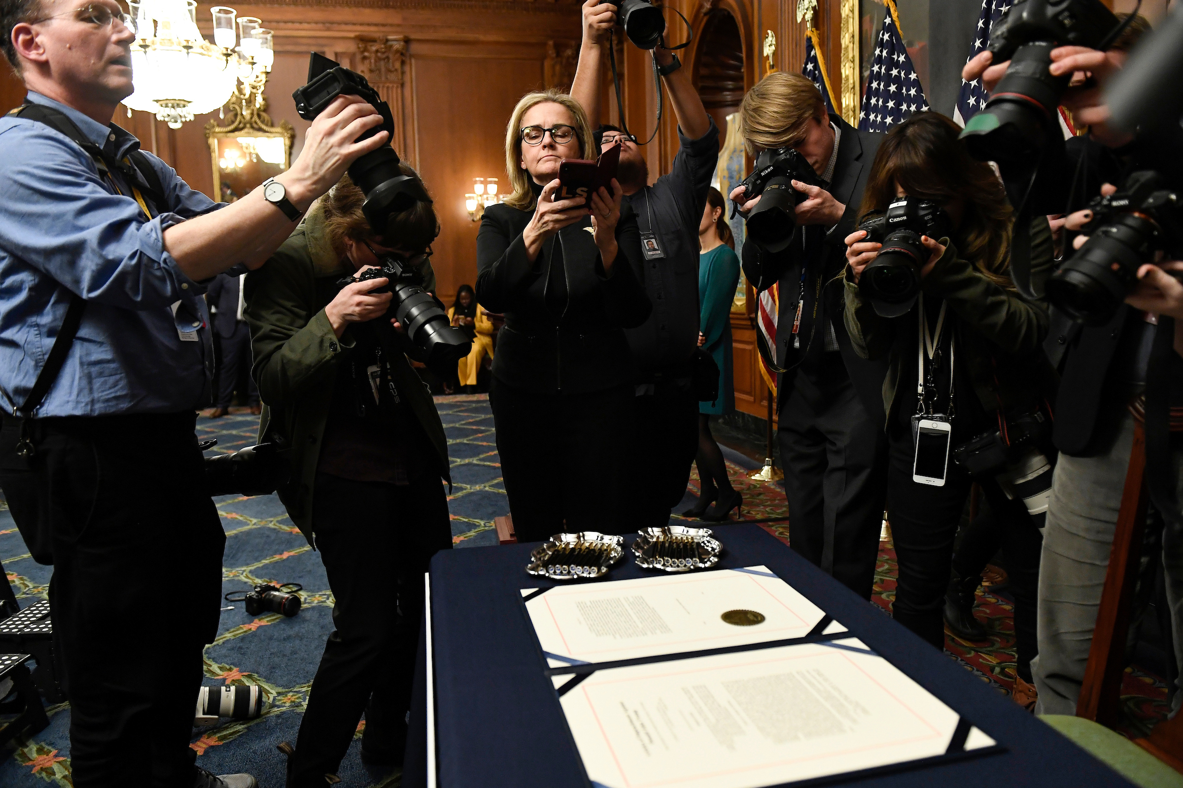 Members of Congress are just like us. Rep. Madeleine Dean snaps a shot of the articles of impeachment on Wednesday. (Caroline Brehman/CQ Roll Call)