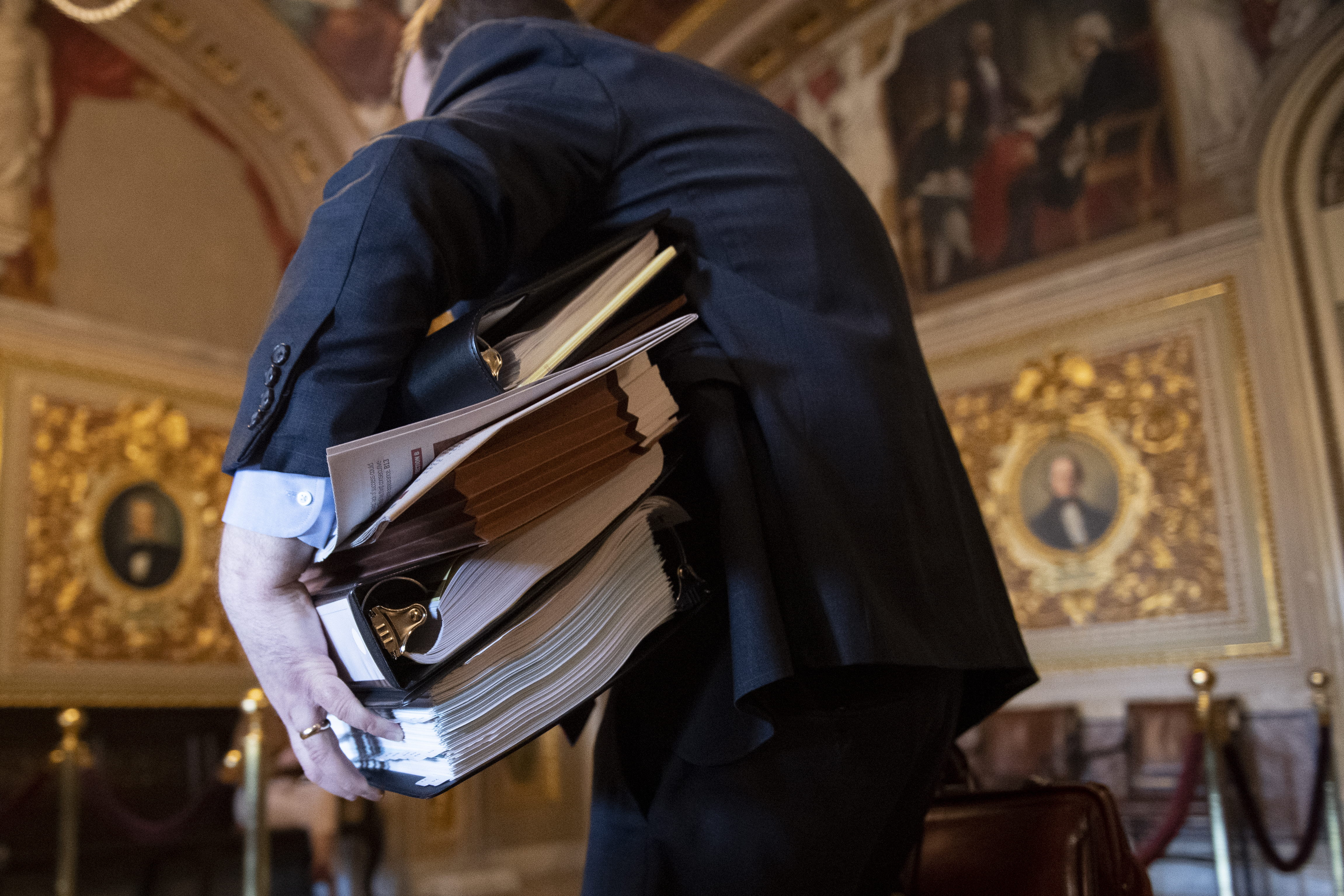 UNITED STATES - JANUARY 30: A staffer carries multiple binders as he walks through the Senate Reception Room before the continuation of the impeachment trial of President Donald Trump on Thursday, Jan. 30, 2020. (Photo by Caroline Brehman/CQ Roll Call)