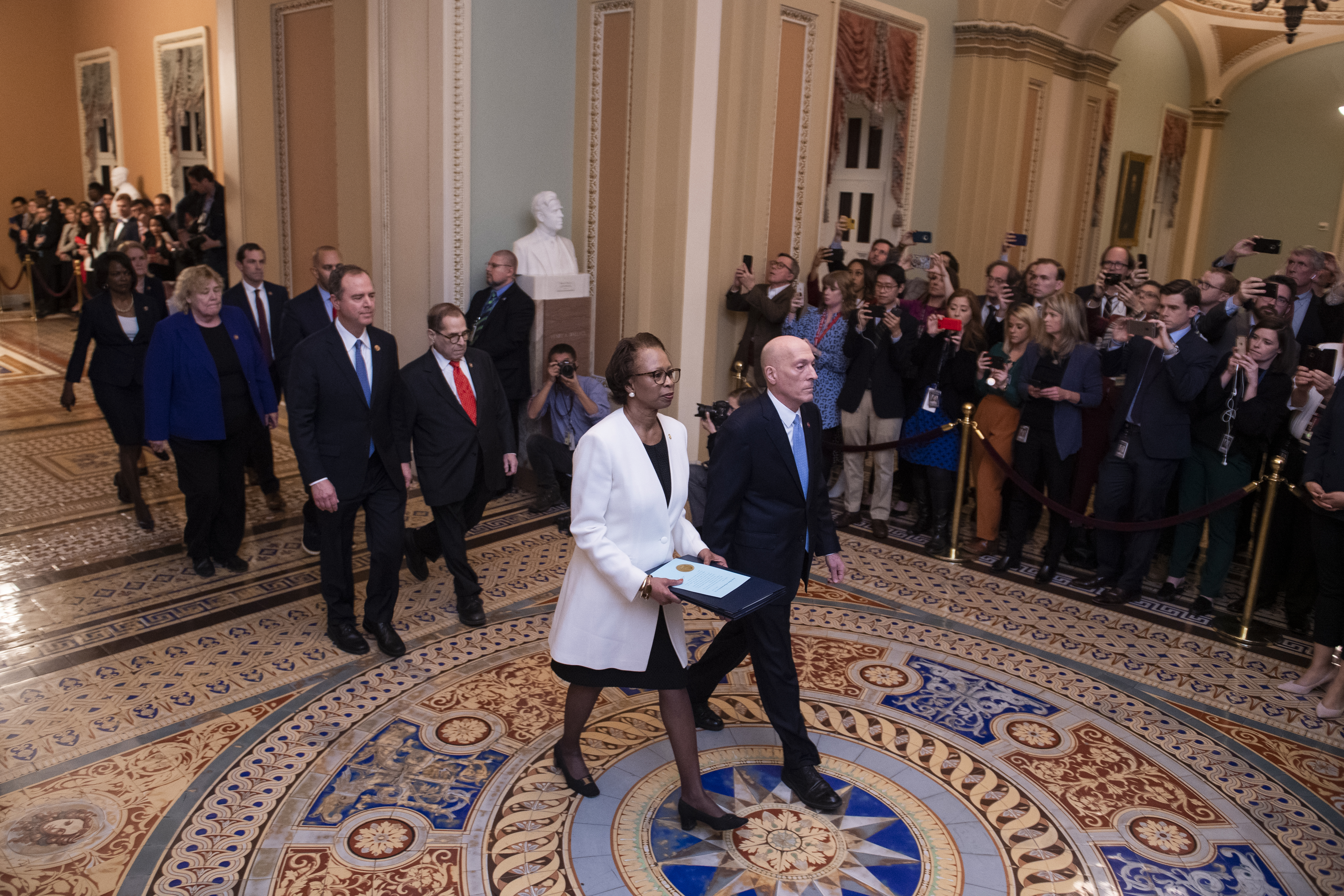 UNITED STATES - JANUARY 15: House Clerk Cheryl Johnson and House Sergeant at Arms Paul D. Irving, followed by impeachment managers Reps. Adam Schiff, D-Calif., Jerrold Nadler, D-N.Y., Zoe Lofgren, D-Calif., Hakeem Jeffries, D-N.Y., Jason Crow, D-Colo., Val Demings, D-Fla., and Sylvia Garcia, D-Texas, walk the articles of impeachment against President Donald Trump from the House to the Senate floor on Wednesday, January 15, 2020. (Photo By Tom Williams/CQ Roll Call)